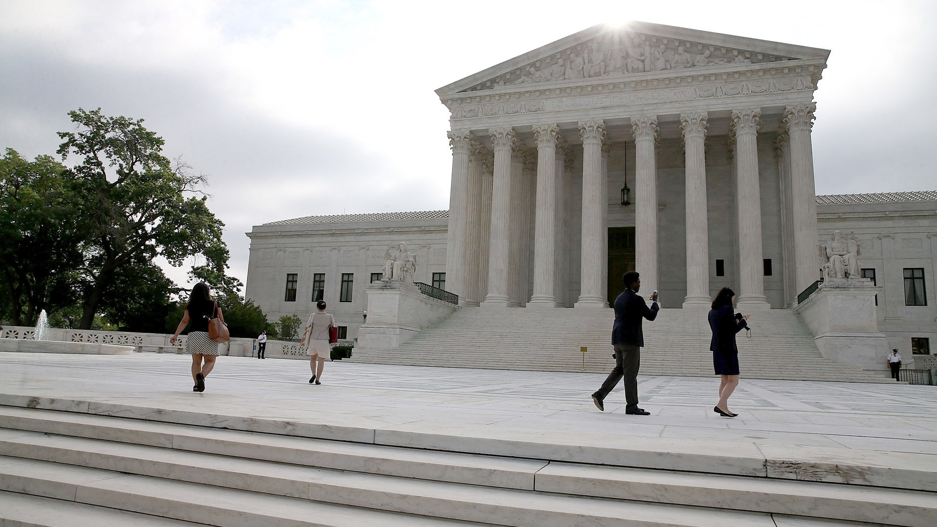 WASHINGTON, DC - JUNE 18:  People gather in front of the Supreme Court Building June 18, 2015 in Washington, DC. This month the high court is expected to hand down its ruling on gay marriage and Obamacare subsidies.  (Photo by Mark Wilson/Getty Images)