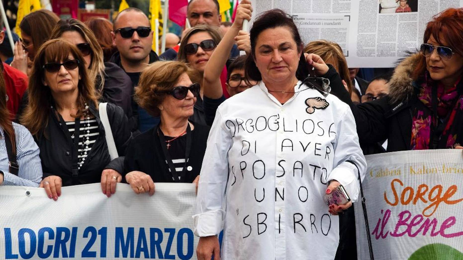 """Rosetta Marino widow of Antonino, a Carabiniere officer killed in 1990, wears a T-shirt reading """"I'm proud to have married a cop"""" during an anti mafia march in Locri,  a base of the 'ndrangheta crime syndicate in Reggio Calabria, Southern Italy, Tuesday, March 21, 2017. On the eve of Tuesday's protest, vandals scrawled graffiti in the mafia stronghold of Locri calling Don Luigi Ciotti, a leading anti-mafia crusader, a cop and demanding """"More work, fewer cops."""" (Marco Costantino/ANSA via AP)"""