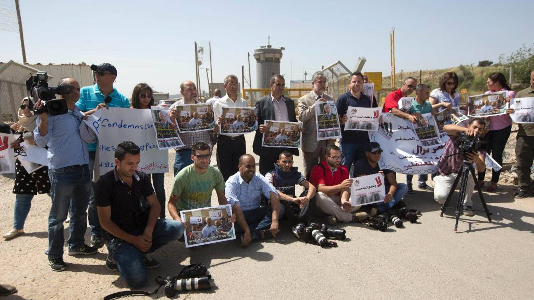Palestinian journalists hold banners during a protest calling for the release of Palestinian journalist Omar Nazzal, who was arrested by Israeli authorities over the weekend, outside Ofer military prison near the West Bank city of Ramallah, Tuesday, April 26, 2016. (AP Photo/Majdi Mohammed)