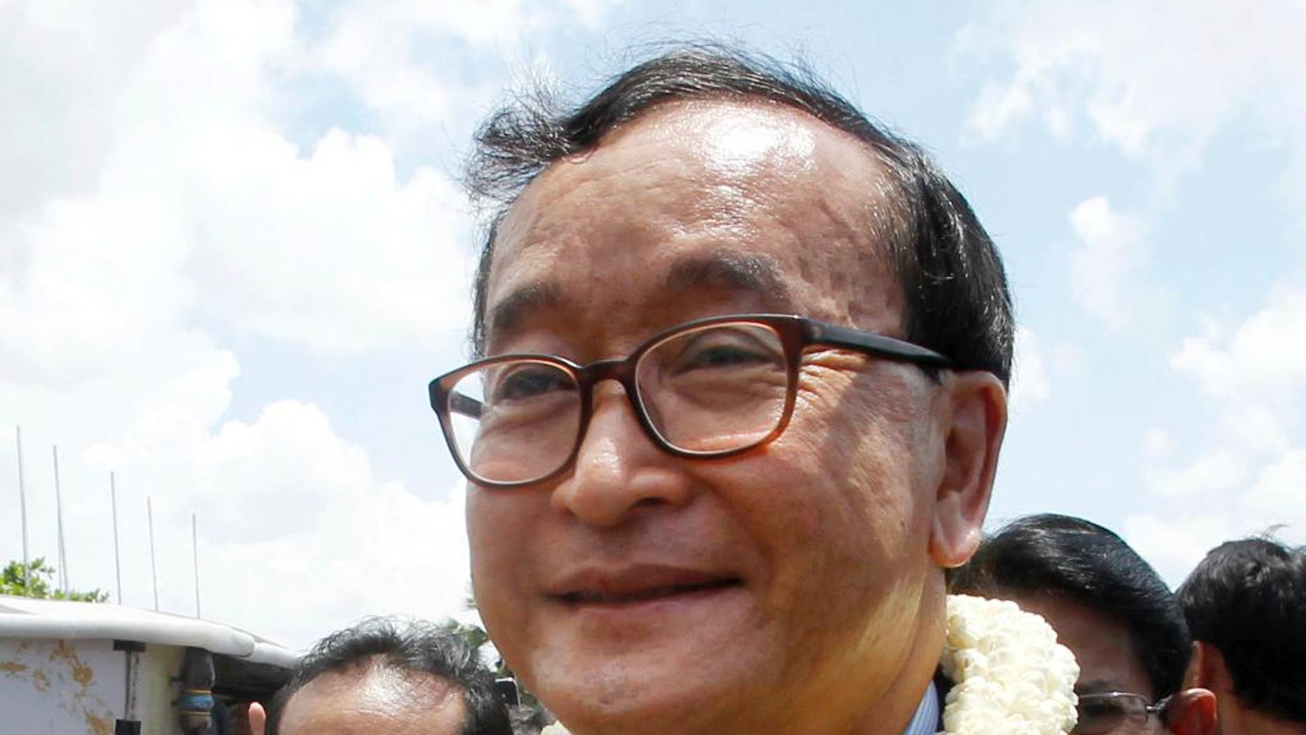 "FILE - In this Aug. 16, 2015, file photo, Sam Rainsy, leader of the opposition Cambodia National Rescue Party, greets his party supporters upon his arrival at Phnom Penh International Airport in Phnom Penh, Cambodia. The Phnom Penh Municipal Court on Tuesday, Nov. 8, 2016, found Sam Rainsy, country's exiled opposition leader, guilty of defamation for alleging that a senior government official sought to inflate Prime Minister Hun Sen's online popularity by buying ""likes"" for his Facebook page. (AP Photo/Heng Sinith, File)"