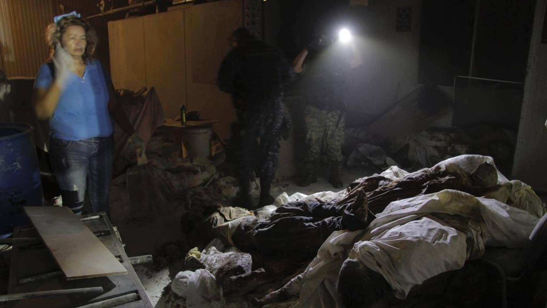 Forensic workers and Mexican army soldiers stand next to a pile of bodies found at the crematorium of an abandoned funeral home near Acapulco, Mexico, early Friday Feb. 6, 2015. Sixty-one decomposed bodies, most of them male, were discovered Thursday evening at the facility, which had been shuttered for about one year, according to a government official. The state of Guerrero, where Acapulco is located, has been shaken by drug-related violence, including the notorious disappearance of 43 college students who allegedly were rounded up by corrupt police on Sept. 26 and handed over to a drug gang. (AP Photo/Bernandino Hernandez)