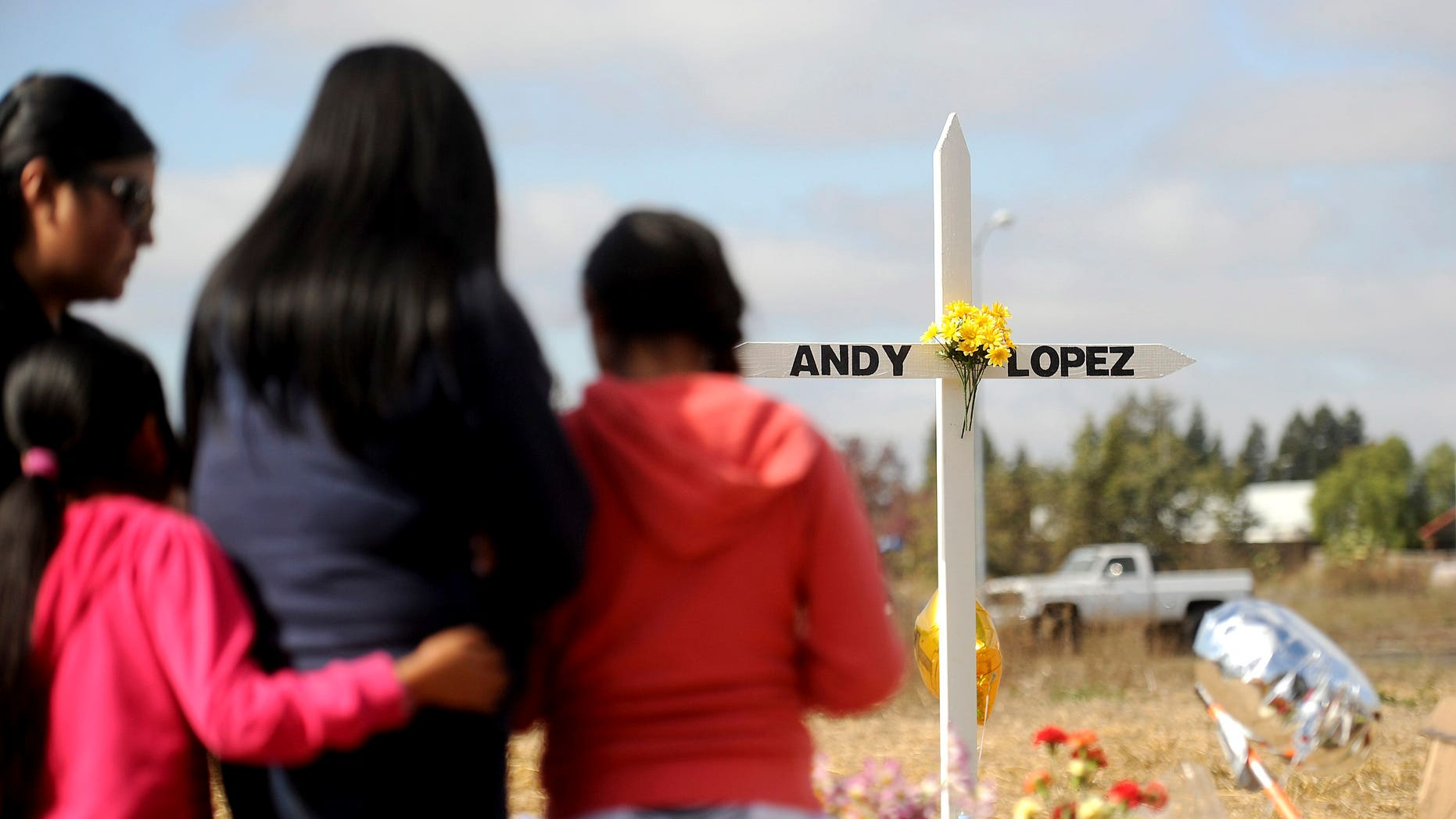 A family pauses at a memorial marking the location where sheriff's deputies shot and killed 13-year-old Andy Lopez in Santa Rosa, California, October 27, 2013.