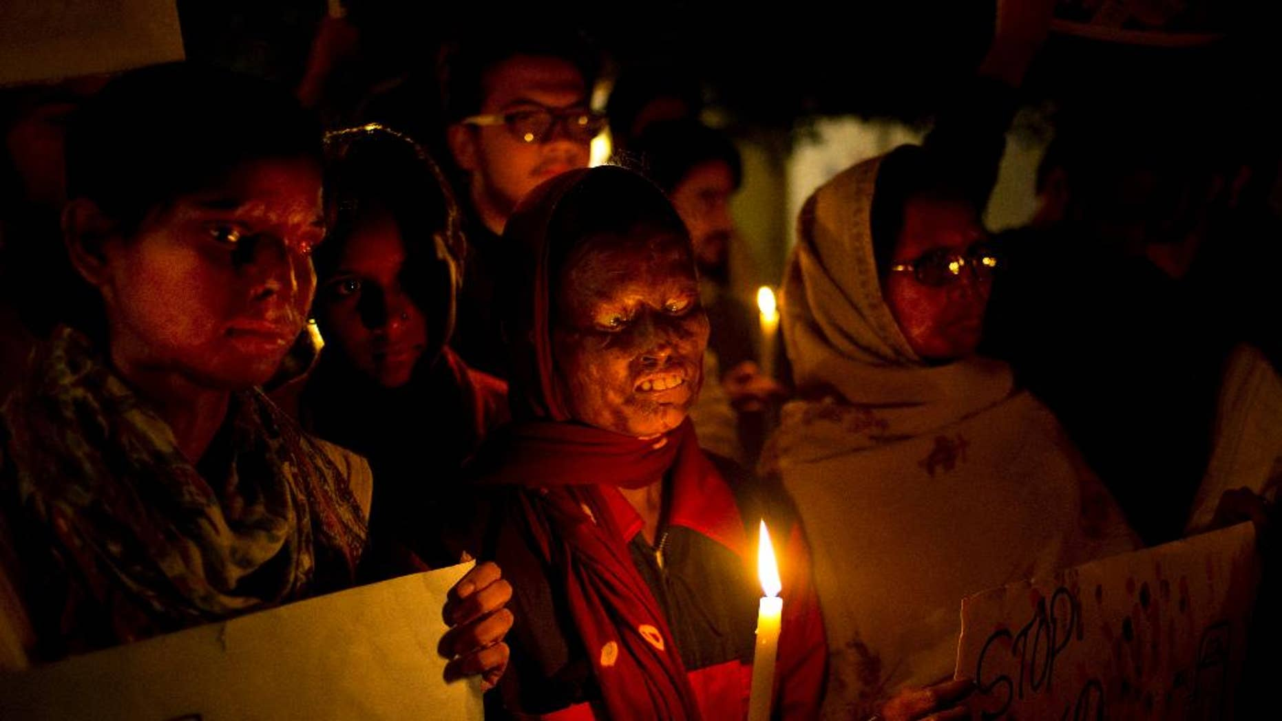 FILE - In this Dec. 16, 2014 file photo, acid attack survivors participate in a candlelit vigil protesting violence against women as they mark the second anniversary of the deadly gang rape of a student on a bus, in New Delhi, India. An Indian court has on Thursday, Sept. 8, 2016, sentenced a man to death for killing his 23-year-old woman neighbor by throwing sulfuric acid at her for refusing to marry him three years ago. This is the first death punishment for an acid attack under stringent laws framed by the government to curb crimes against women following a fatal gang rape of a young woman in a moving bus in New Delhi in 2012. (AP Photo/Saurabh Das, File)