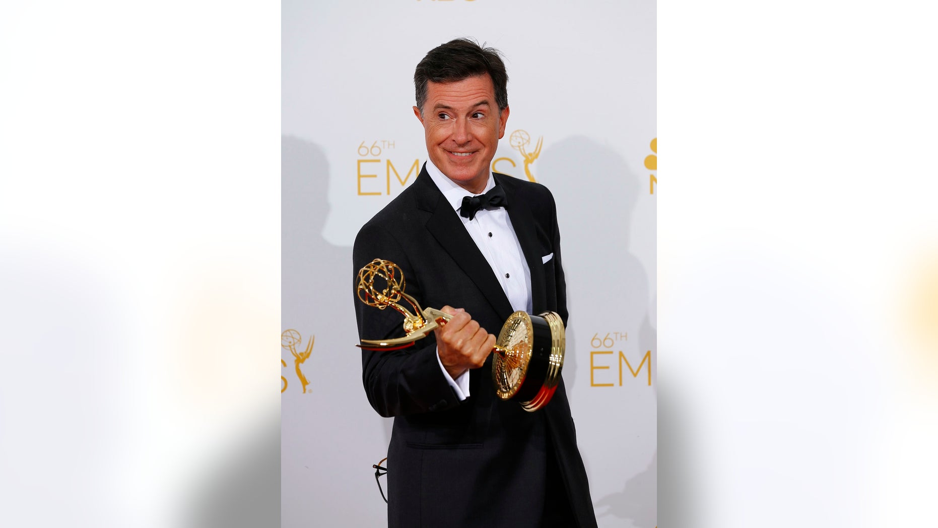 """Stephen Colbert poses with his Outstanding Variety Series award for Comedy Central's """"The Colbert Report"""" at the 66th Primetime Emmy Awards in Los Angeles, California August 25, 2014. The host responded to Donald Trump's tweet about his time hosting the 2017 awards."""