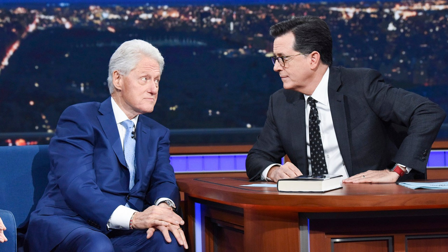 Former President Bill Clinton, left, appears with host Stephen Colbert while promoting his book 'The President is Missing,' on 'The Late Show with Stephen Colbert,' Tuesday, June 5, 2018 in New York.