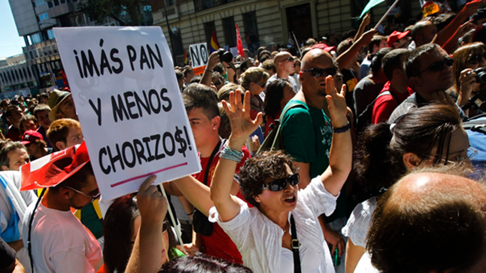 """People shout slogans and show a banner reading """"more bread and less thieves"""" protest against austerity measures applied by the Spanish government, in  Columbus Square in Madrid, Spain, Saturday, Sept. 15, 2012. Tens of thousands of people from all over the country converged on Madrid to hold a large anti-austerity demonstration on Saturday. By mid-morning several major roads had been blocked as buses unloaded protesters at 10 rendezvous points from which marches began. The demonstration was called to protest government cuts during the country's financial crisis. (AP Photo/Andres Kudacki)"""