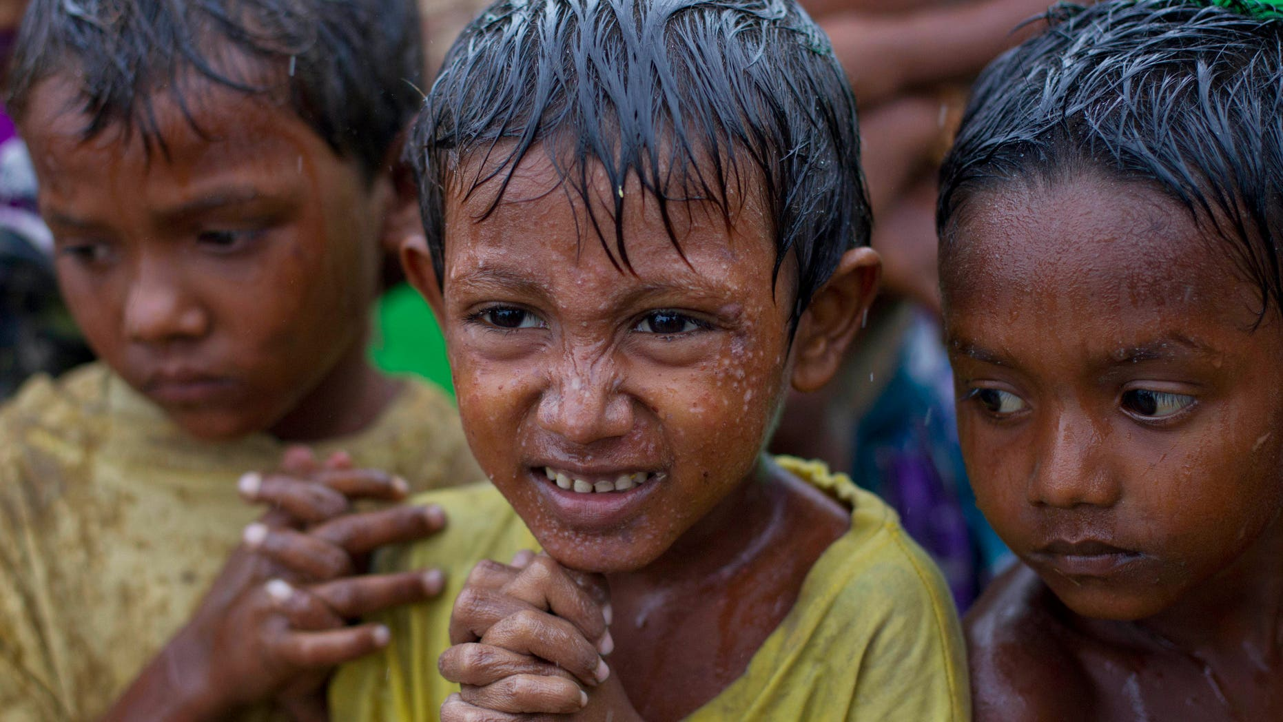 May 14, 2013: Internally displaced Rohingya boys shiver in rain in a makeshift camp for Rohingya people in Sittwe, northwestern Rakhine State, Burma, ahead of the arrival of Cyclone Mahasen.