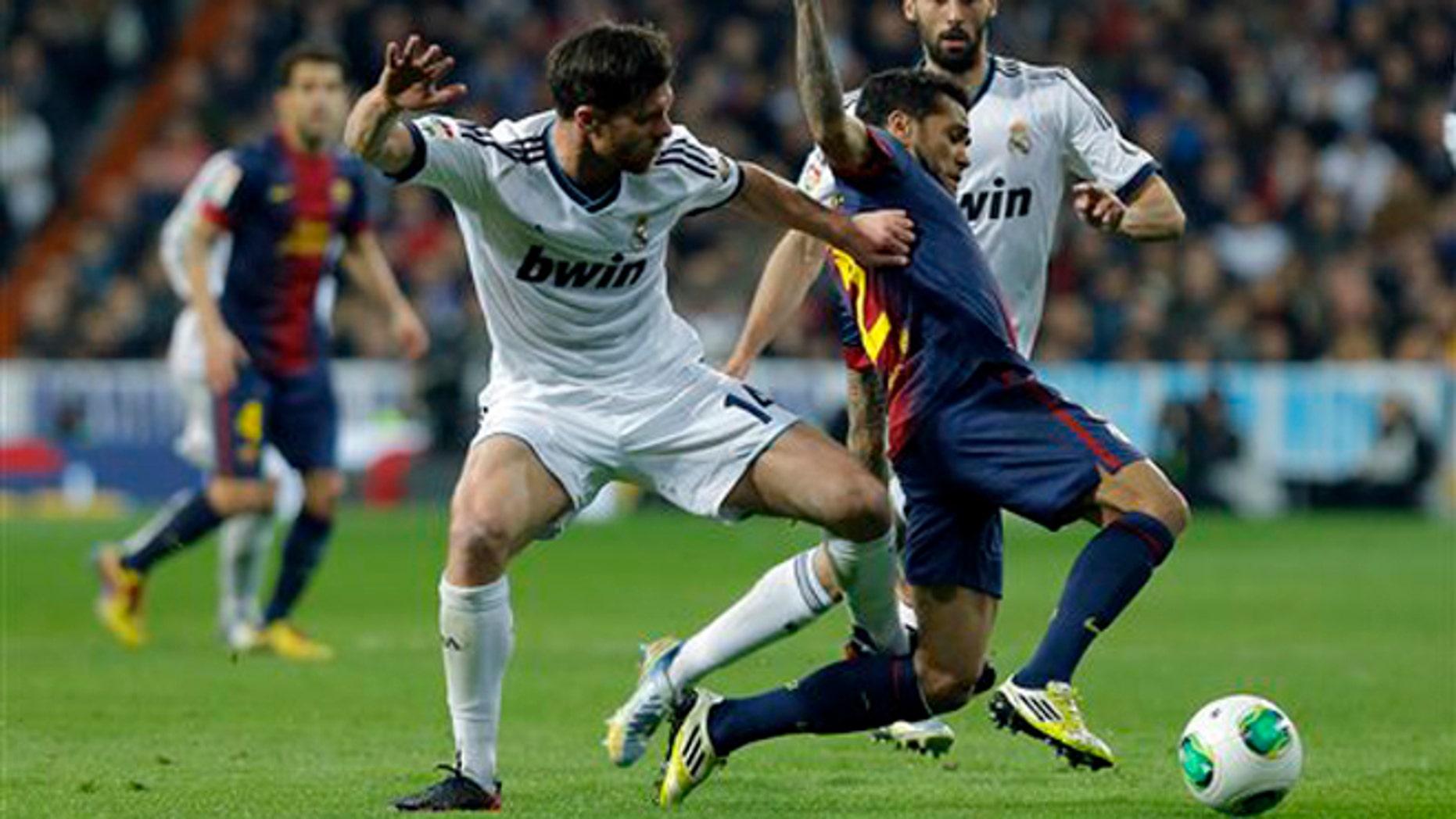 El jugador brasileño del Barcelona, Dani Alves, centro, disputa un balón en un partido contra Real Madrid por las semifinales de la Copa del Rey el miércoles, 30 de enero de 2013, en Madrid. (AP Photo/Andres Kudacki)