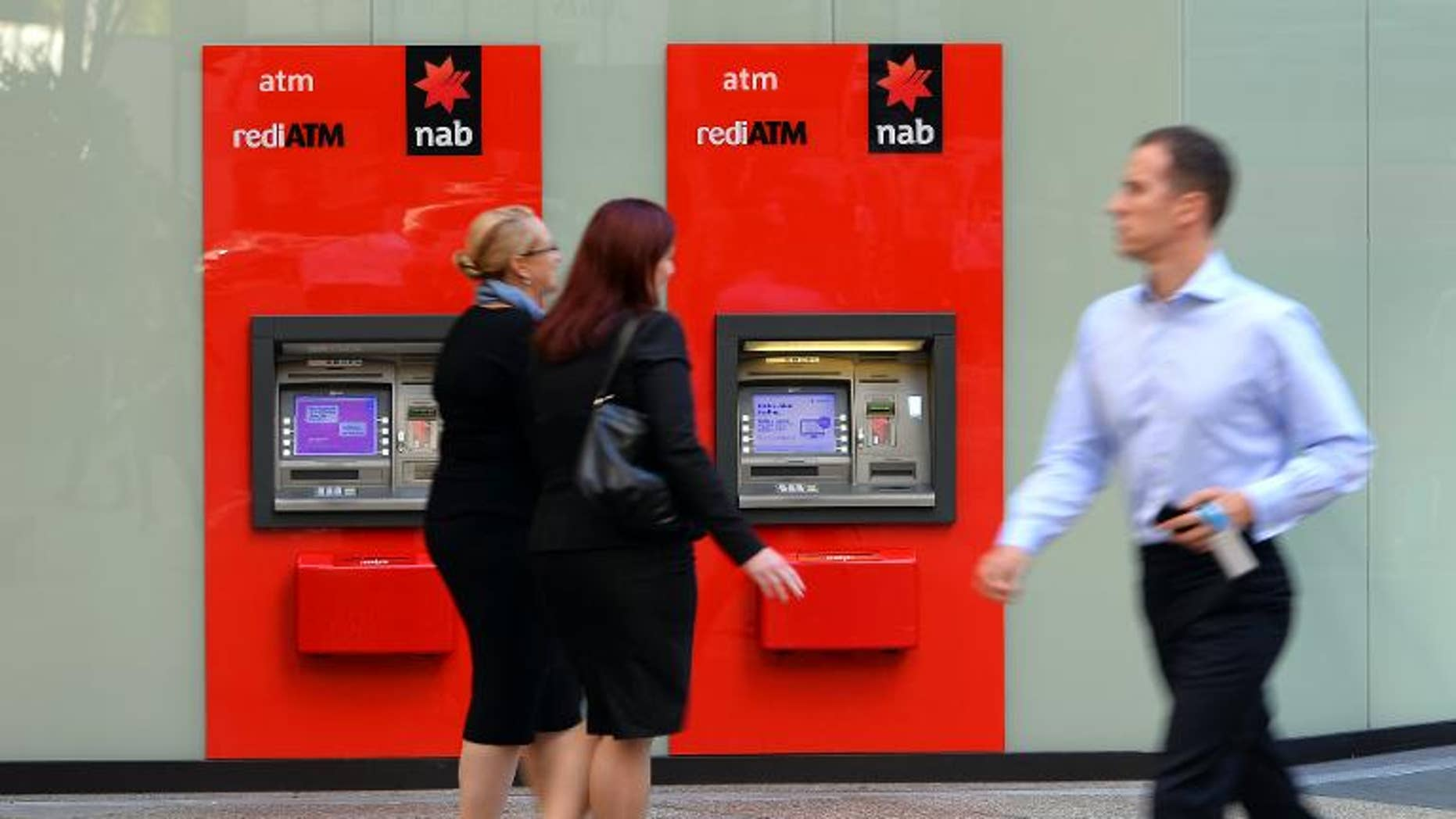 People walk past National Australia Bank (NAB) automated teller machines in the central business district of Sydney on May 9, 2013. British regulators Thursday said they had fined NAB-owned Clydesdale Bank almost ??9.0 million.