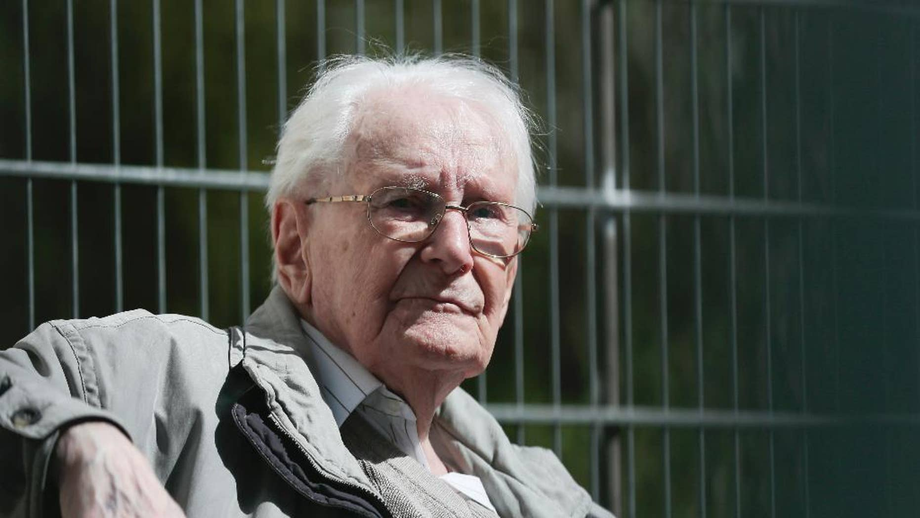 Former SS guard Oskar Groening sits in ths sun during the noon break of the trial against him in Lueneburg, northern Germany, Tuesday, April 21, 2015.  93-years-old Groening faces 300,000 counts of accessory to murder at the trial, which will test the argument that anyone who served as a guard at a Nazi death camp was complicit in what happened there. Groening said he bears a share of the moral guilt for atrocities at the camp, but told judges it is up to them to decide whether he deserves to be convicted as an accessory to murder.  (AP Photo/Markus Schreiber)