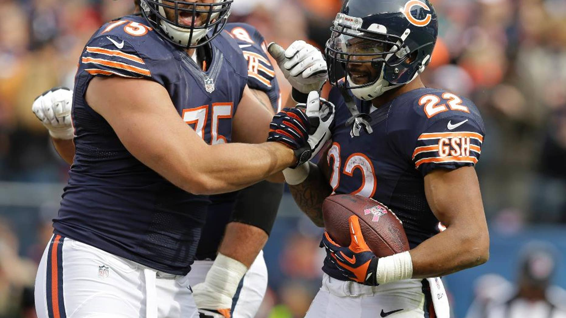 Chicago Bears running back Matt Forte (22) celebrates a touchdown with guard Kyle Long (75) during the second half of an NFL football game against the Miami Dolphins Sunday, Oct. 19, 2014 in Chicago. (AP Photo/Nam Y. Huh)