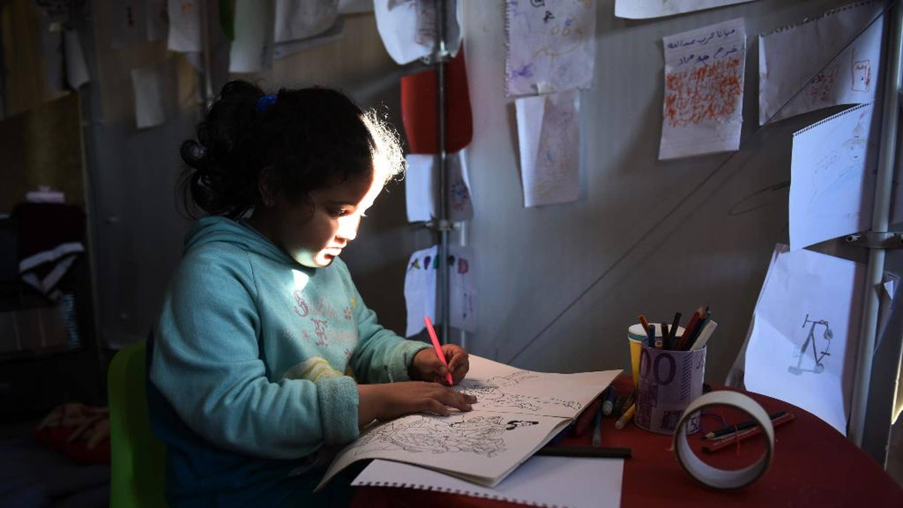 A Syrian girl draws  at a refugee camp near the northern Greek village of Idomeni near to southern Macedonia, Monday, Nov. 9, 2015. Migrants are facing long waits to cross Greece's border with Macedonia after a four-day ferry strike ended and eased a bottleneck on the country's eastern Aegean islands, where the vast majority of people arrive from nearby Turkey. (AP Photo/Giannis Papanikos)