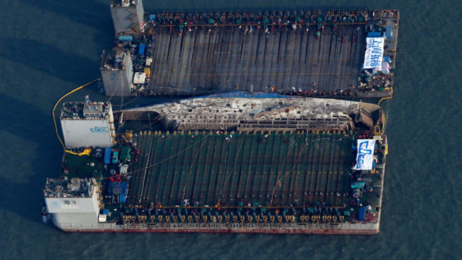 MARCH 23: Workers try to raise the sunken Sewol ferry, center, between two barges during the salvage operation in waters off Jindo, South Korea