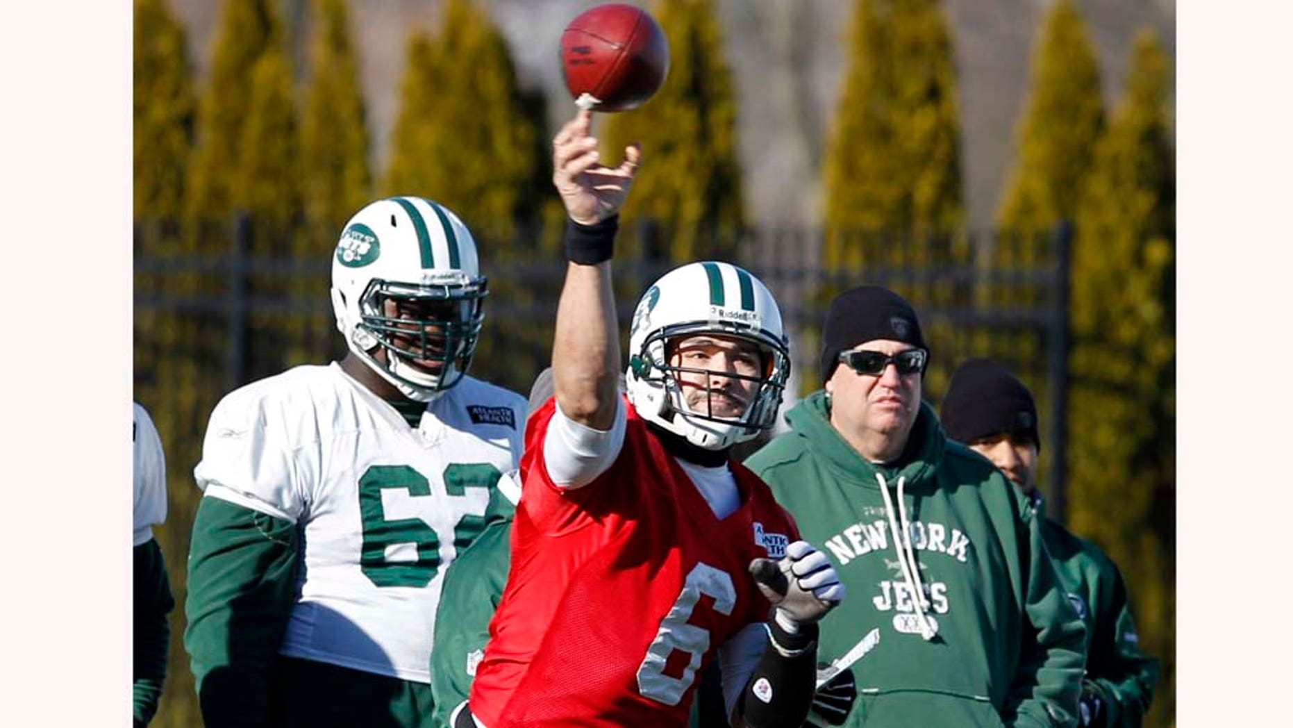 As New York Jets head coach Rex Ryan, right, and lineman Vladimir Ducasse, left,  look on, quarterback Mark Sanchez throws a pass during practice Friday, Jan. 14, 2011, in Florham Park, N.J. The Jets play the New England Patriots in the AFC Divisional playoff game Sunday. (AP Photo/Mel Evans)