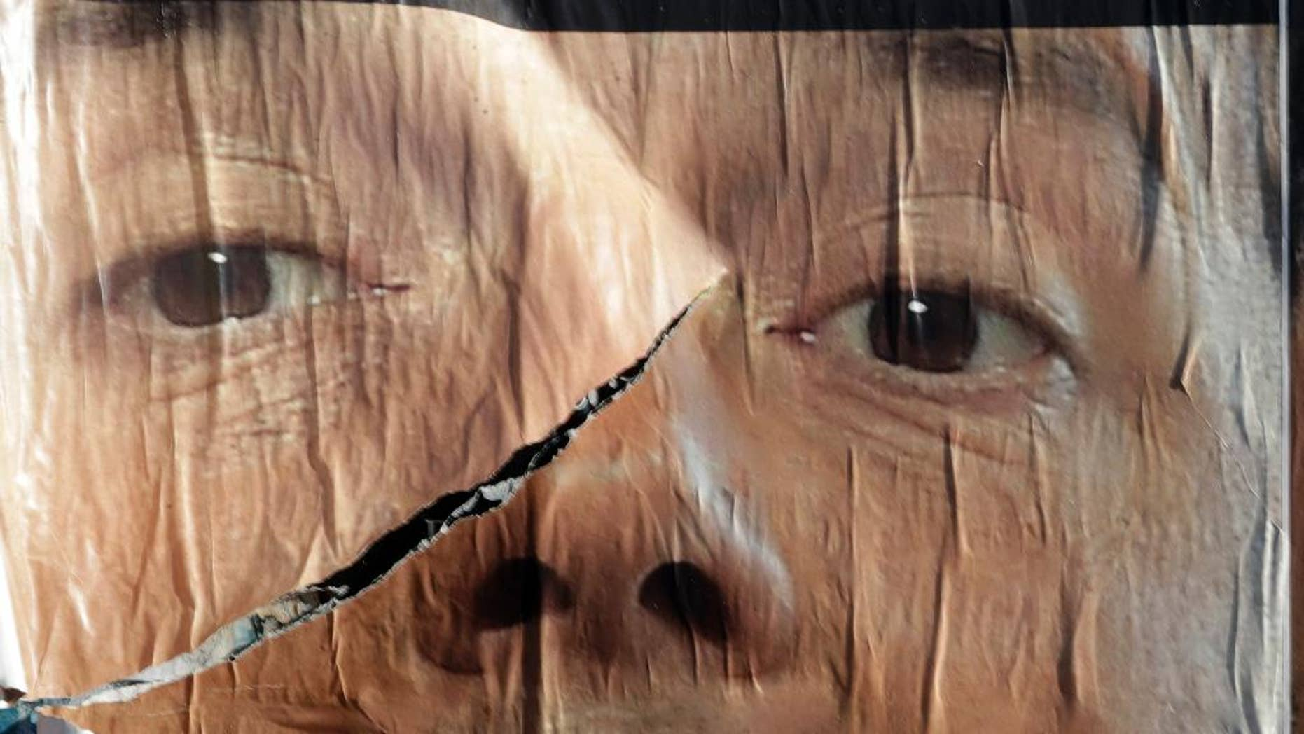 A torn anti-referendum poster shows Premier Matteo Renzi, in Rome, Monday, Dec. 5, 2016. Italian voters dealt Premier Renzi a resounding rebuke early Monday by rejecting his proposed constitutional reforms, plunging Europe's fourth-largest economy into political and economic uncertainty. (AP Photo/Gregorio Borgia)