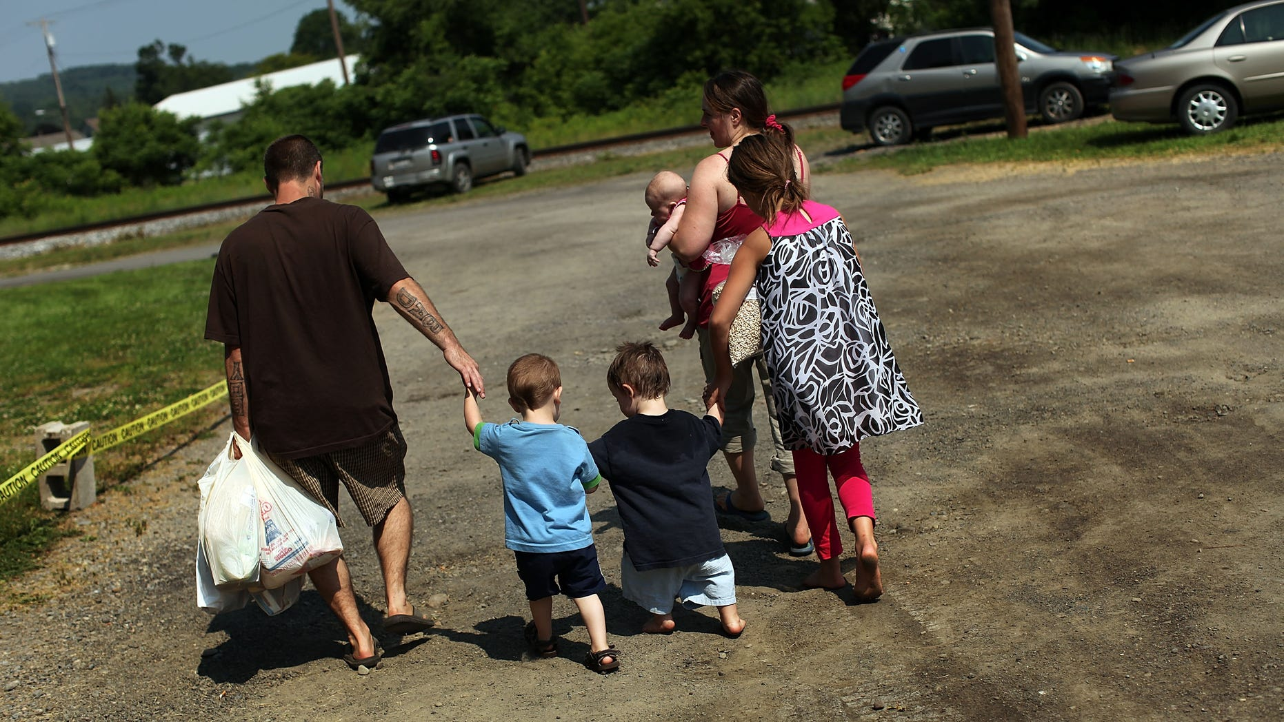 OSWEGO, NY - JUNE 20: Members of the Dolan family walk home with bags of food after a food distribution by the Food Bank of the Southern Tier Mobile Food Pantry on June 20, 2012 in Oswego, New York. The mobile food pantry program was introduced in 2007 in the Southern Tier of New York and covers nearly 4,000 predominately rural miles. The converted beverage truck delivers fresh produce, dairy products and other grocery items to individuals and families in need. The pantry typically distributes for a period of two hours and provides 100 to 160 families with food. According to the 2010 Census, 15.72% the population serviced by the mobile pantry live at or below the federal poverty level. According to statistics presented at a recent U.S. Senate committee hearing, almost one in seven Americans are living below the poverty line with a significant number of them being children.  (Photo by Spencer Platt/Getty Images)