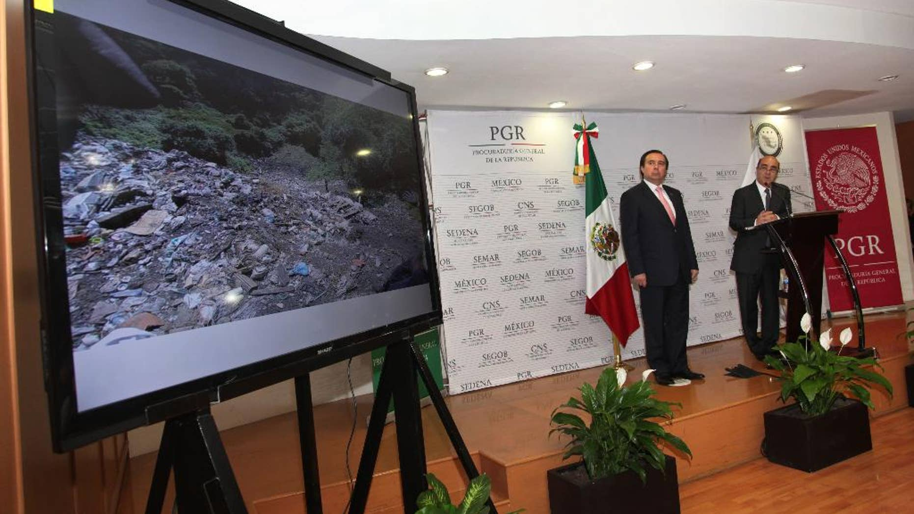 FILE - In this Dec. 7, 2014, file photo, Mexico's Attorney General, Jesus Murillo Karam, right, flanked by Tomas Zeron director of Mexico's Criminal Investigation Agency, speaks during a news conference in Mexico City. The Attorney General's Office has announced on Wednesday, Sept. 14, 2016, the resignation of Tomas Zeron, whose dismissal had been demanded by the families of 43 college students who disappeared two years ago. (AP Photo/Marco Ugarte, File)