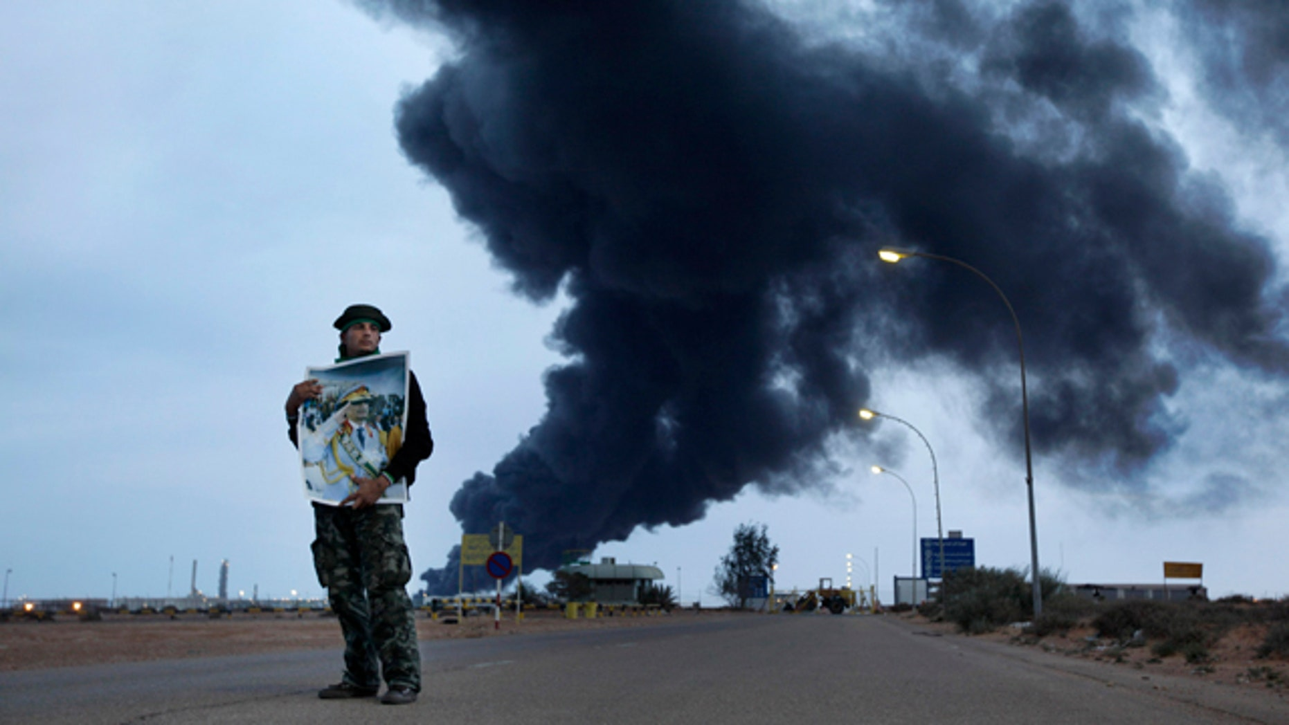 March 12, 2011: A pro-Gadhafi fighter holds a poster of Libyan Leader Moammar Gadhafi as black plume of smoke rises from the burning oil refinery as they are pictured during a government-organized visit for foreign media in Ras Lanouf, Libya