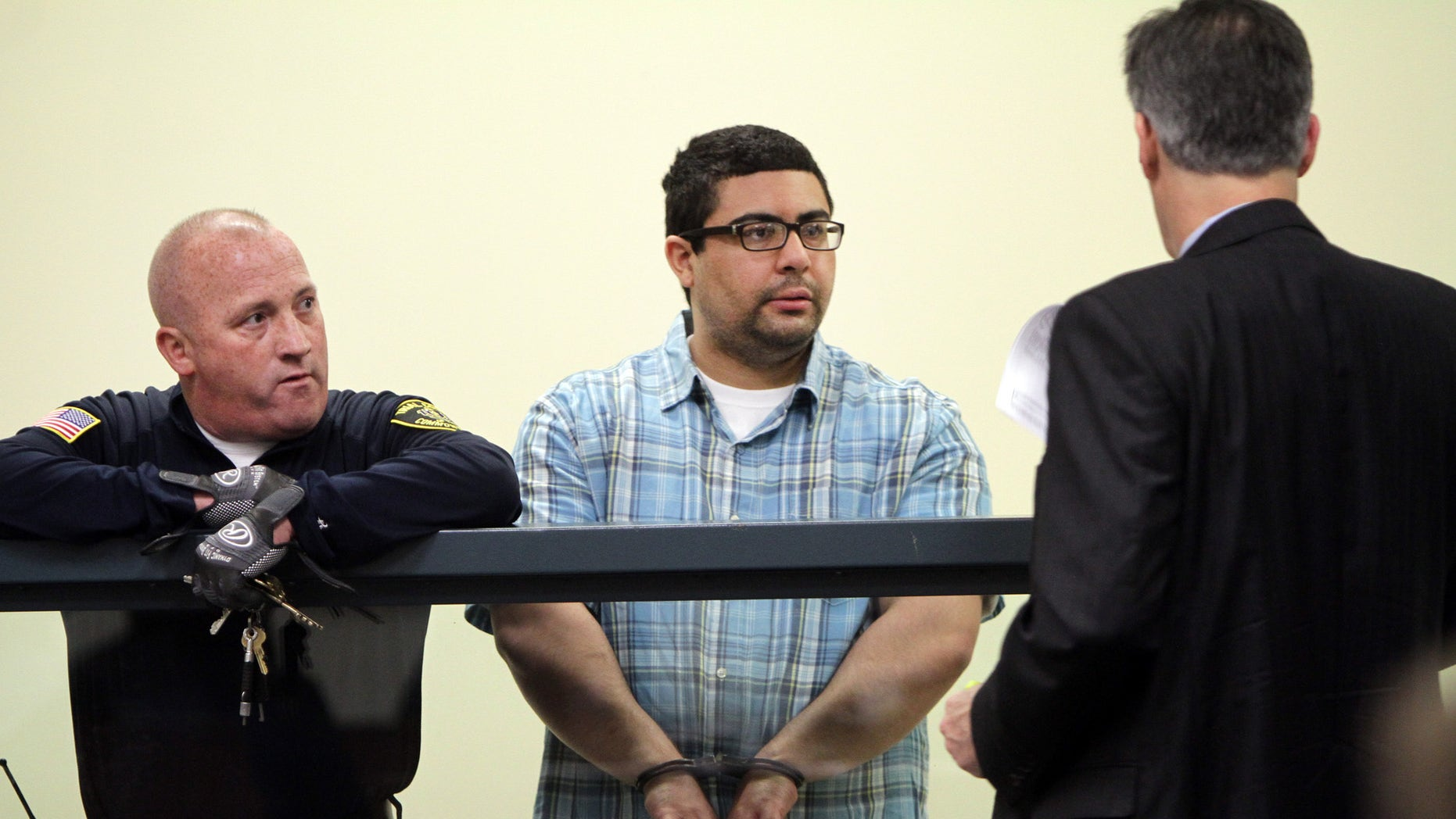 Carlos Colina, center, speaks with his attorney John Cunha, Jr., right, during his arraignment in Cambridge District Court in Medford, Mass., Monday, April 6, 2015.  Colina was charged with being an accessory after the crime of assault and battery causing serious bodily injury and the improper disposal of human remains, after the discovery of human remains in Cambridge on Saturday. (AP Photo/The Boston Herald, Chitose Suzuki, Pool)