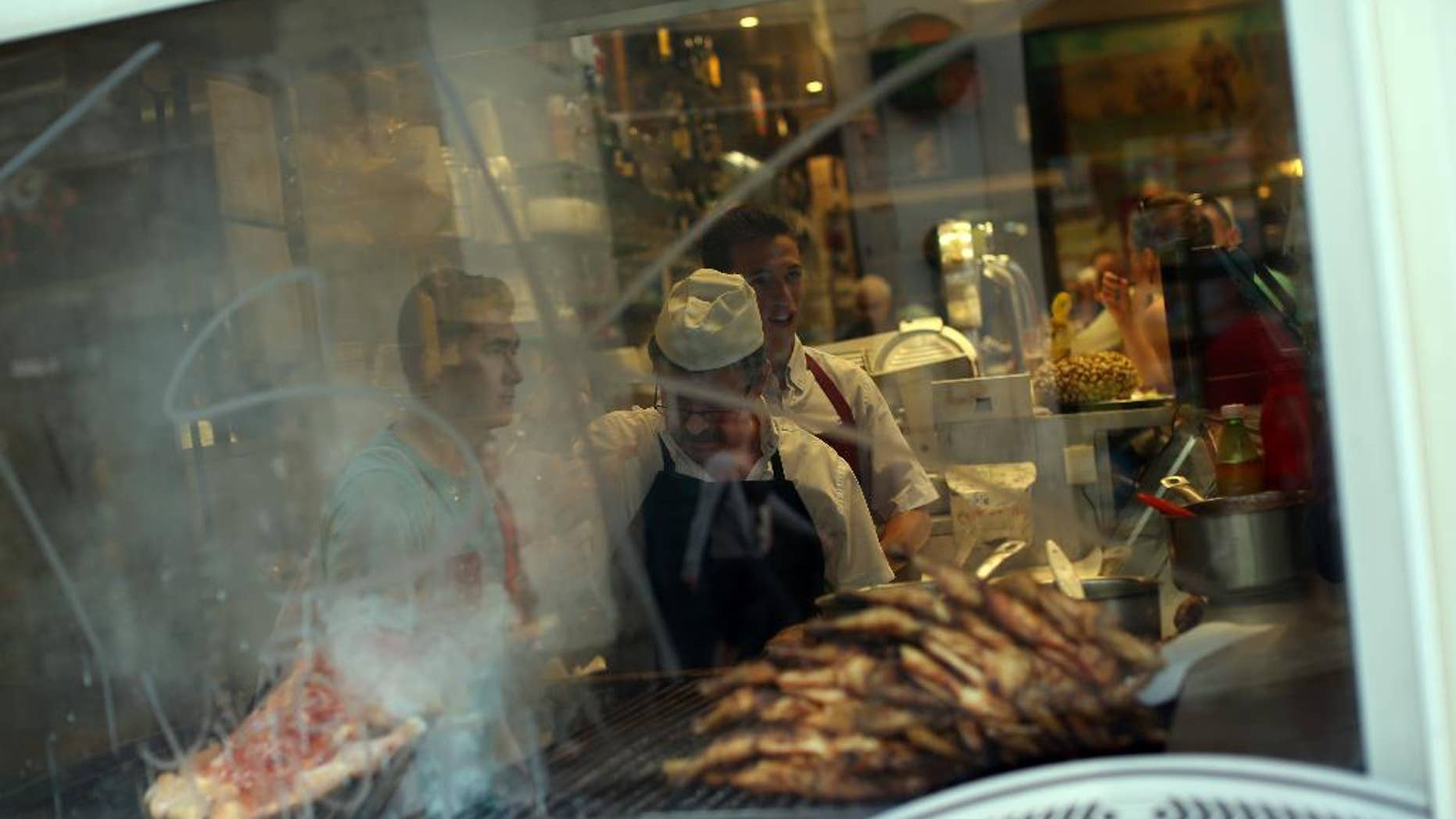 """A man grills meat in a barbecue of a Portuguese traditional food restaurant in Lisbon, Thursday, May 21, 2015. European Central Bank head Mario Draghi said that """"growth is too low everywhere"""" in Europe despite a modest recovery, during an ECB's conference on inflation and unemployment in Sintra, Portugal. (AP Photo/Francisco Seco)"""