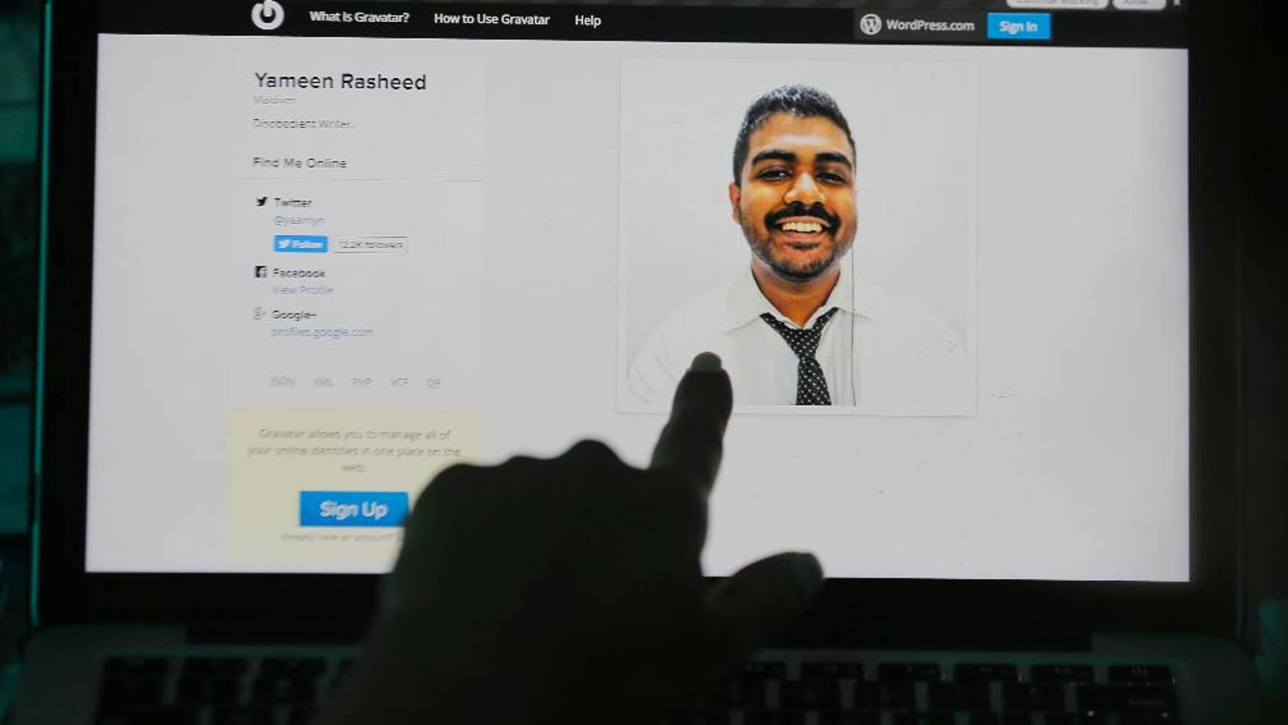 """A Sri Lankan woman points to a portrait of Maldivian blogger Yameen Rasheed on his blog """"The Daily Panic"""" in Colombo, Sri Lanka, Sunday, April 23, 2017. Police in the Maldives said in a statement that Rasheed was found Sunday morning with multiple stab wounds in a house in the capital, Male. He died at a hospital. (AP Photo/Eranga Jayawardena)"""