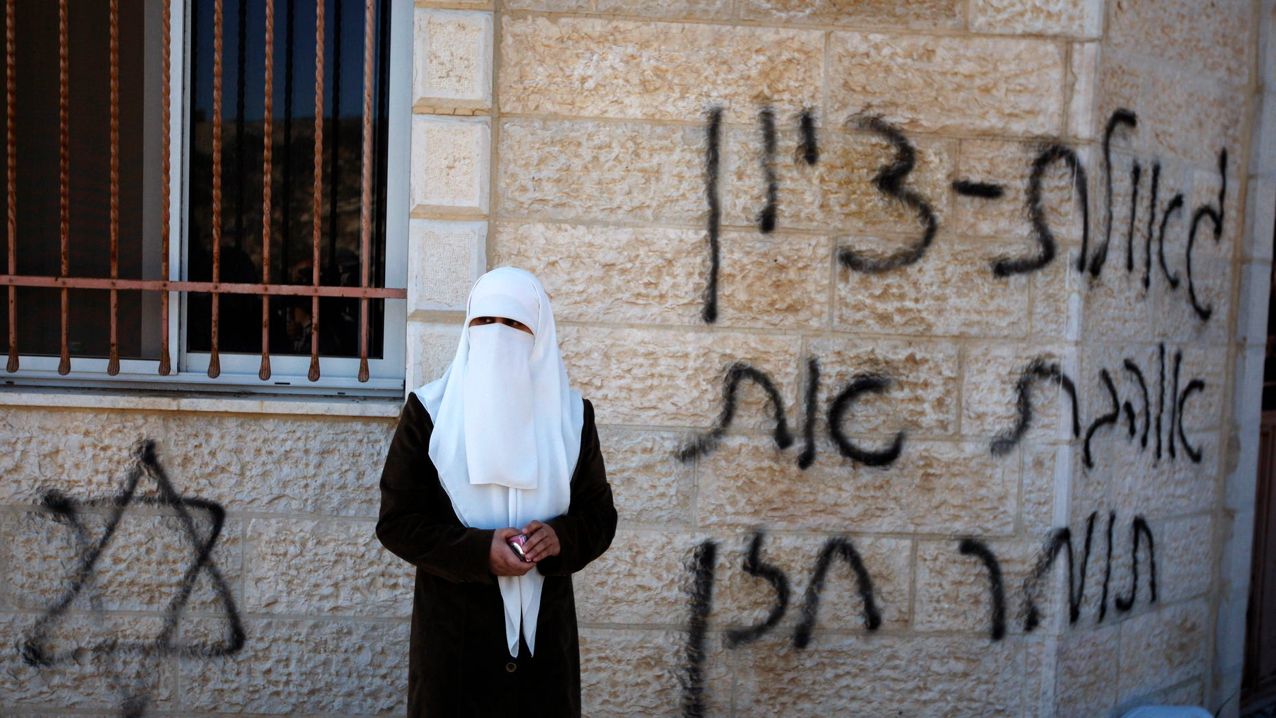 """A Palestinian woman stands next to a vandalized mosque in the West Bank village of Burka, near Ramallah, Thursday, Oct. 10, 2013. The Hebrew graffiti reads, """"Redemption of Zion, I love Tomer Hazan."""" Hazan was an Israeli soldier killed by a Palestinian in a West Bank village in September 2013. Palestinian residents of the village said that masked Jewish settlers torched three cars and defaced a mosque during an overnight attack. (AP Photo/Majdi Mohammed)"""