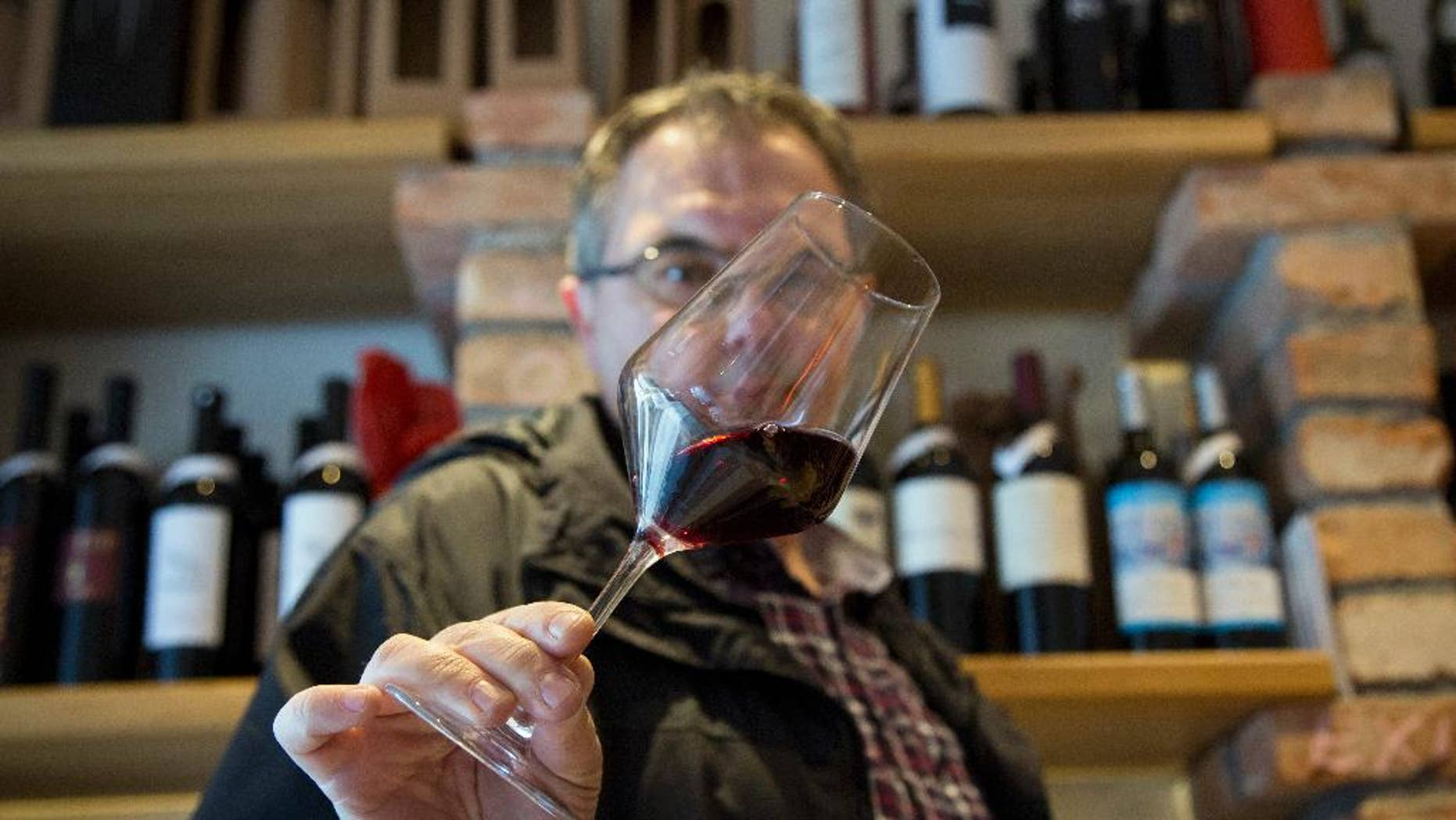 """FILE - In this Wednesday, March 1, 2017 file photo, Robert Samek, a sommelier, inspects a glass of red wine at his wine shop in Zagreb, Croatia. Slovenian winemakers say they expect the European Commission to suspend the procedure of issuing a permit to Croatia to use the Teran red wine brand in the 28-nation bloc. The head of a Slovenian group to protect Teran, Marjan Colja, told The Associated Press on Friday, March 10 that his group has """"no doubt"""" documentation presented by Croatia has been """"partly forged."""" (AP Photo/Darko Bandic, file)"""