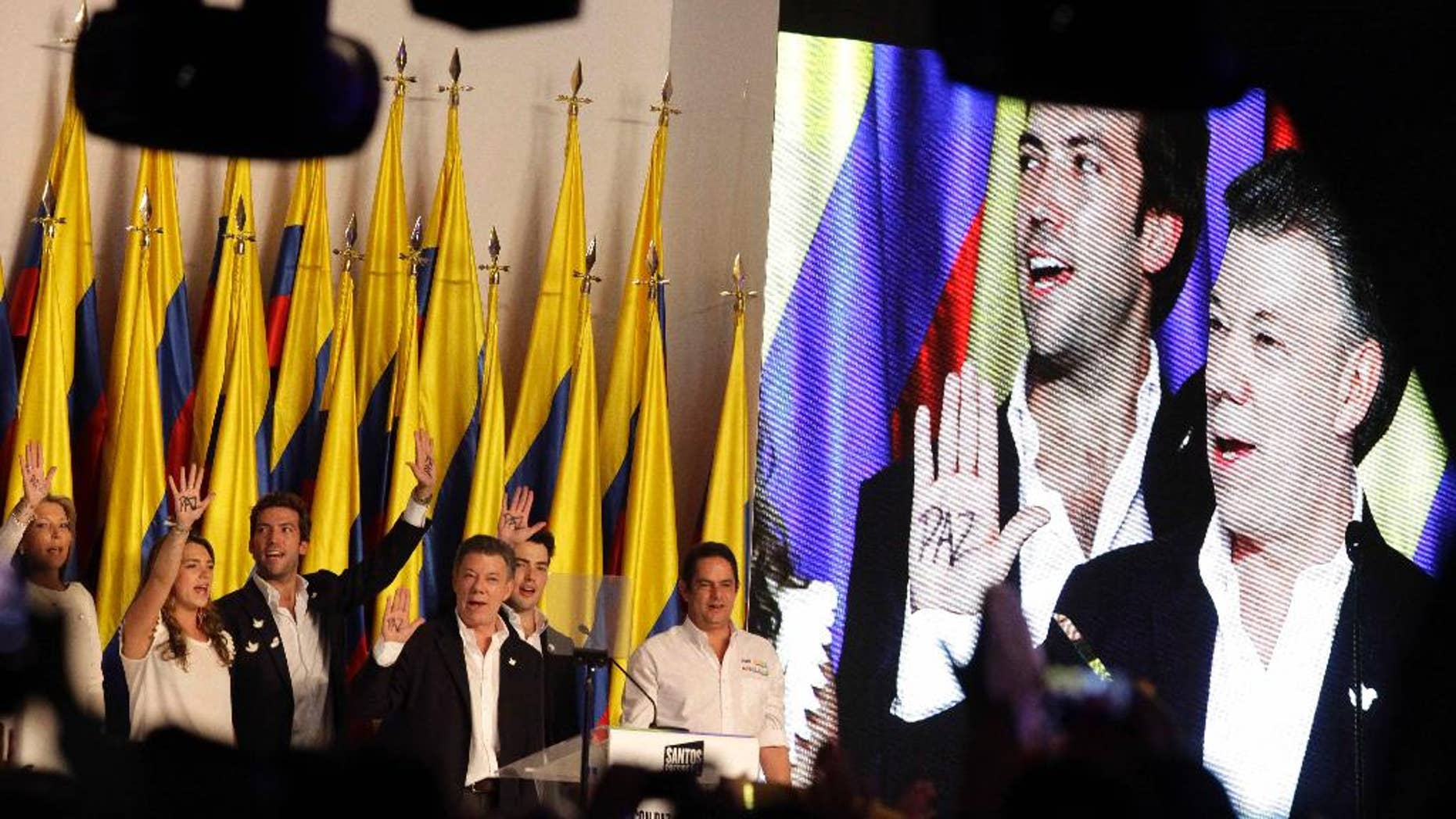 President Juan Manuel Santos, on screen at far right, celebrates winning the presidential runoff election, surrounded by his family at his campaign headquarters in Bogota, Colombia, Sunday, June 15, 2014. Behind Santos on the screen is his son Martin Santos. Santos defeated challenger Oscar Ivan Zuluaga, of the Democratic Center, and won a second four-year term. (AP Photo/Javier Galeano)