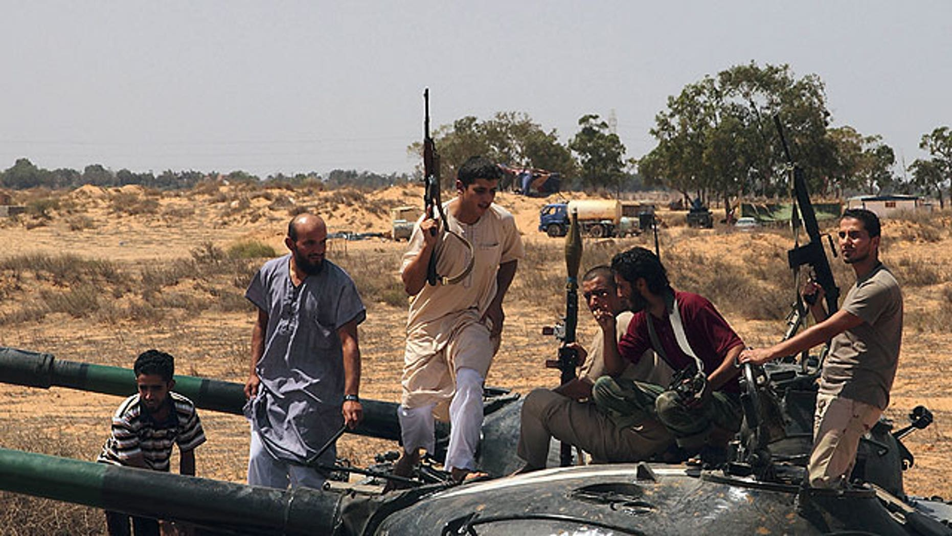 September 1: Freedom fighters climb on a tank for a lookout at a defensive outpost, some 30 kilometers outside Misrata, Libya.