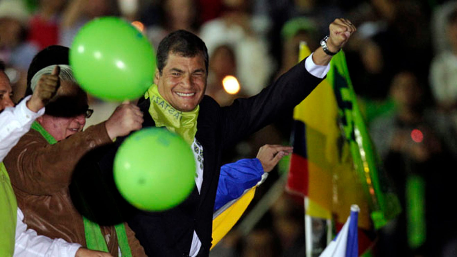 Ecuador's President Rafael Correa lifts his fist as he arrives atop a car to participate in a in event marking the fifth anniversary of his administration in Cuenca, Ecuador, Saturday, Jan. 14, 2012. (AP Photo/Dolores Ochoa)