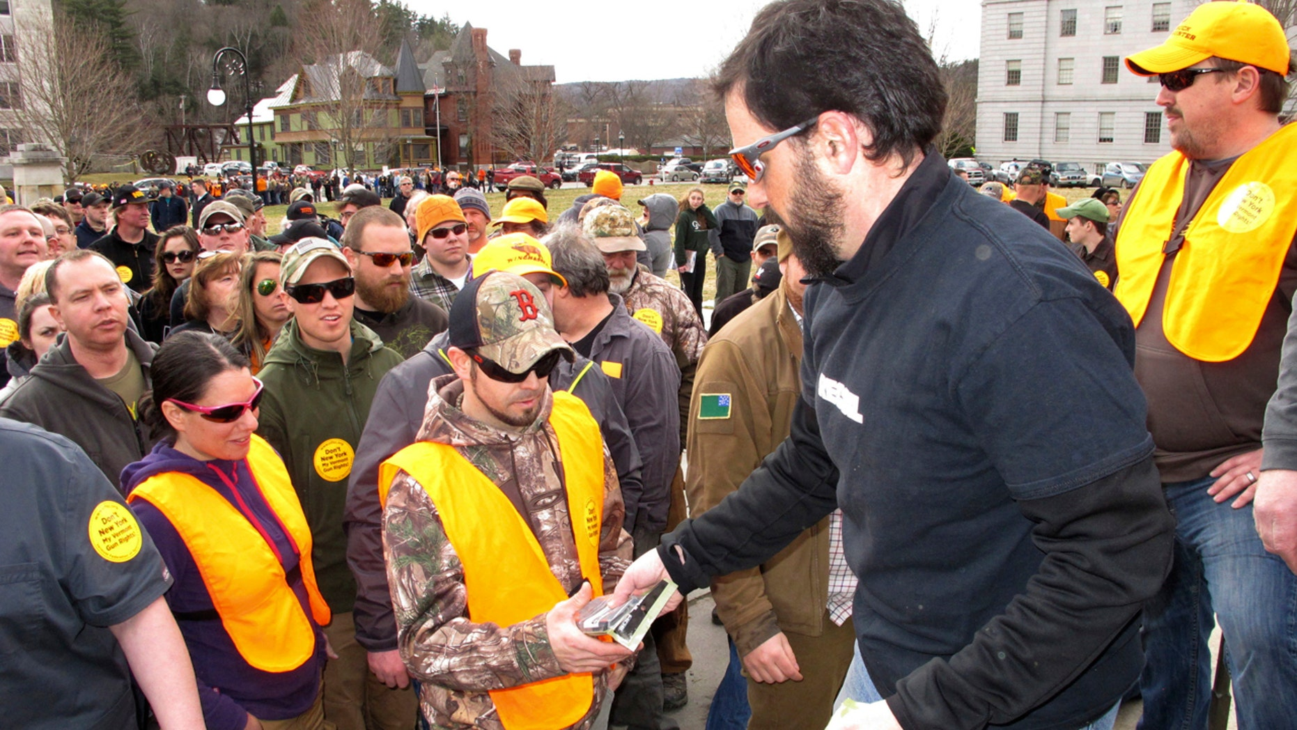 Rob Curtis, executive editor of a firearms magazine, handed out 30-round magazines at a gun rights event outside the Vermont Statehouse in Montpelier, Vt., on March 31 to oppose gun restriction legislation approved by state lawmakers.