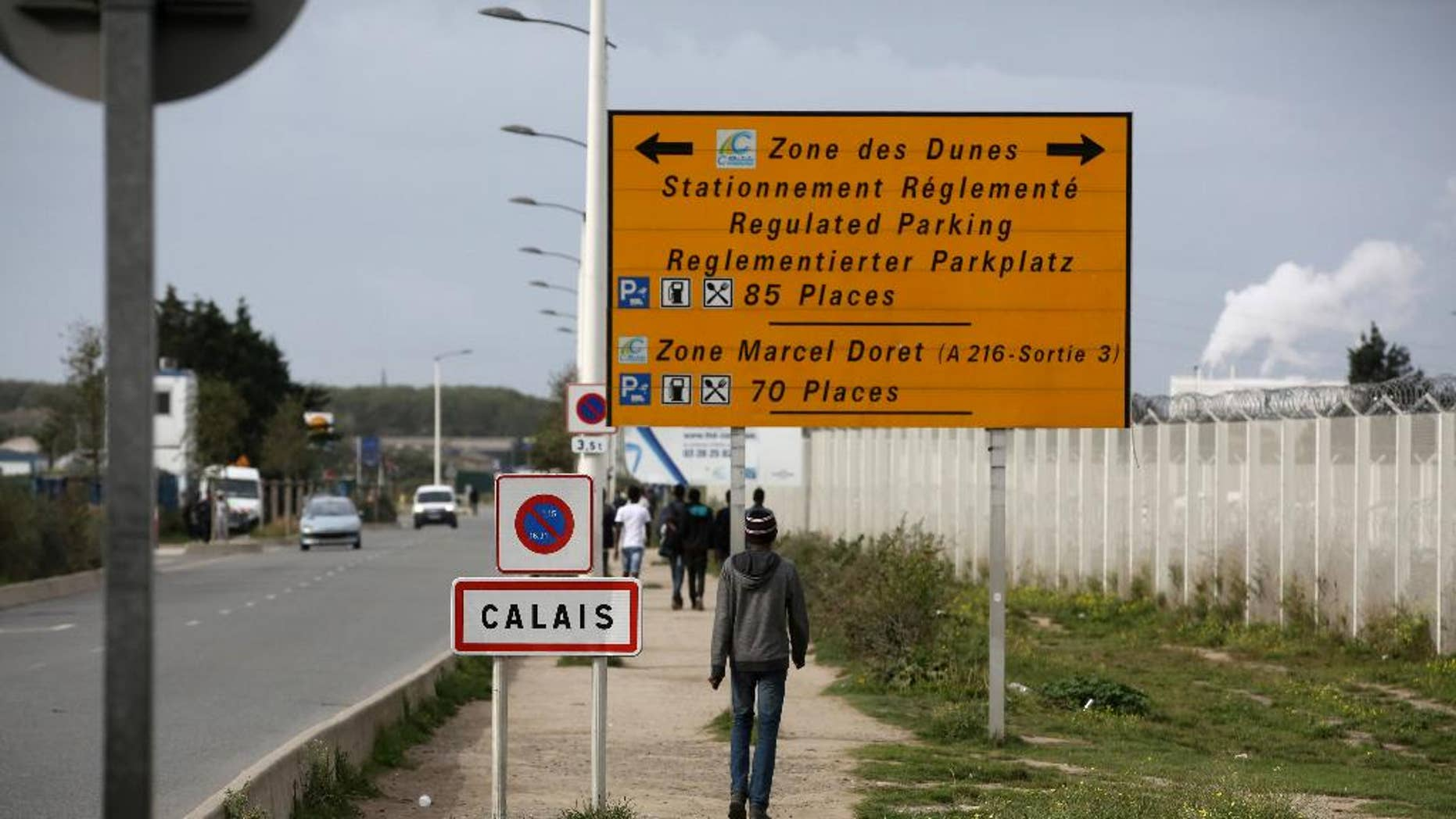 FILE - In this Monday, Sept. 26, 2016 file photo, a migrant walks outside the makeshift camp in Calais, northern France. French authorities have arrested and convicted a top smuggler and his accomplice who had reigned over desperate migrants trying to sneak to Britain.  (AP Photo/Thibault Camus, File)