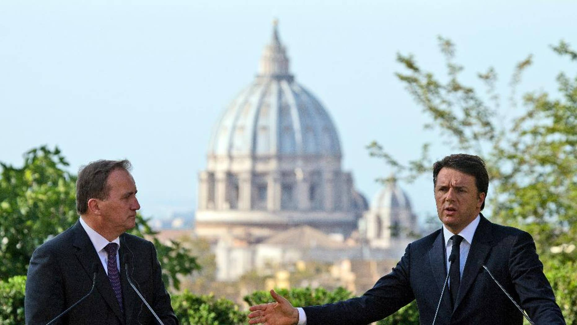 Italian Premier Matteo Renzi, right, and Swedish Prime Minister Stefan Lofven, backdropped by the St. Peter's Basilica, talk to journalists during a press conference at the end of their meeting, at Rome's Villa Panphilii, Wednesday, July 6, 2016.  (AP Photo/Andrew Medichini)