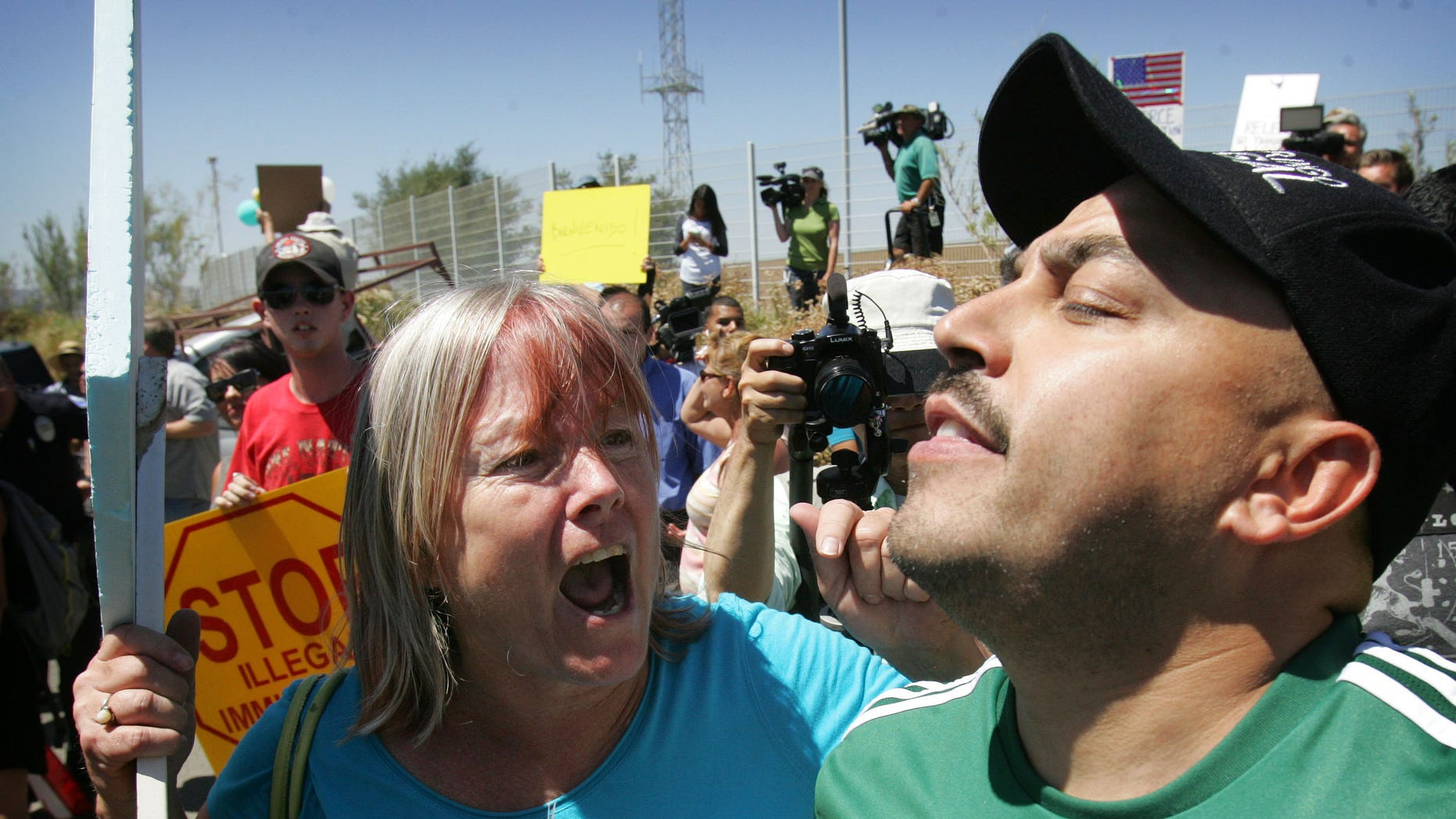 An unidentified protester, left, argues with American citizen Lupillo Rivera, brother of Mexican-American singer Jenni Rivera.