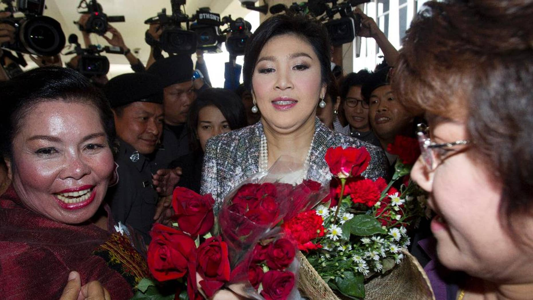 Thailand's former Prime Minister Yingluck Shinawatra, center, receives flowers from her supporters as she leaves parliament in Bangkok, Thailand, Thursday, Jan. 22, 2015. Thailand's military-appointed legislature is set to vote on impeachment against Yingluck over a government's rice subsidy scheme on Friday. AP Photo/Sakchai Lalit)