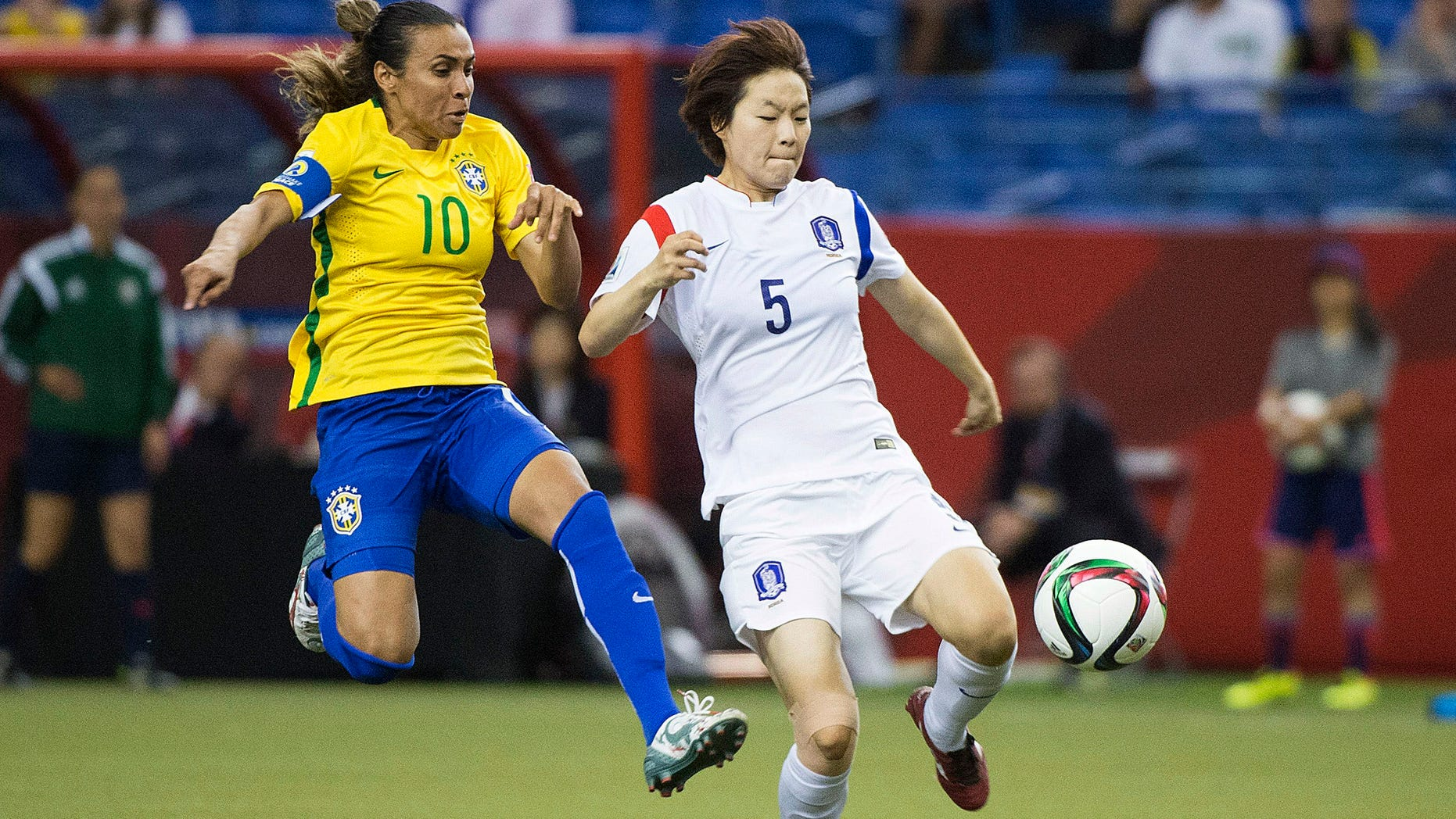 Brazil's Marta (10) challenges South Korea's Kim Doyeon during the second half of a FIFA Women's World Cup soccer match Tuesday, June 9, 2015, in Montreal, Canada. (Graham Hughes/The Canadian Press via AP)