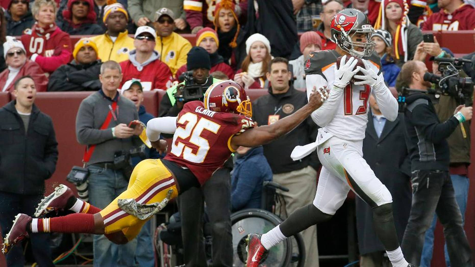 Tampa Bay Buccaneers wide receiver Mike Evans (13) pulls in a touchdown pass under pressure from Washington Redskins free safety Ryan Clark (25) during the second half of an NFL football game in Landover, Md., Sunday, Nov. 16, 2014. (AP Photo/Alex Brandon)