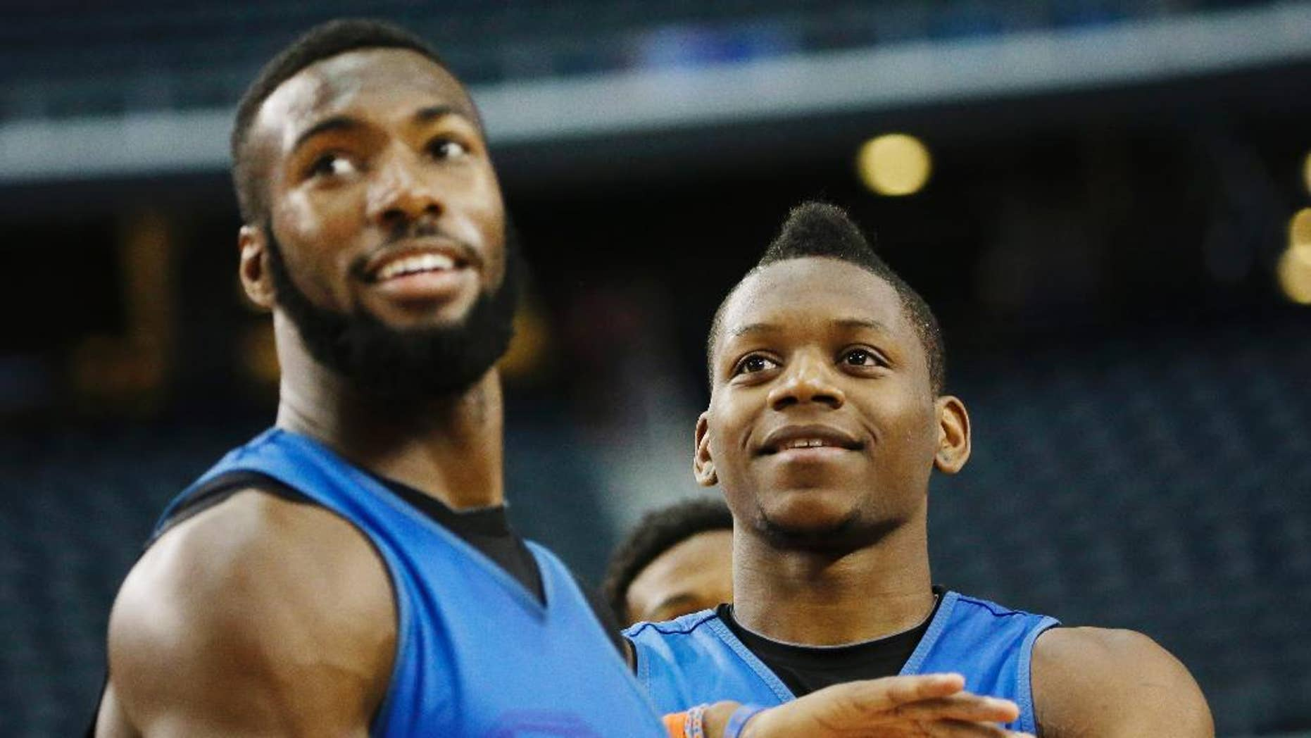 Florida center Patric Young, left, and forward Will Yeguete joke around during practice for their NCAA Final Four tournament college basketball semifinal game Friday, April 4, 2014, in Dallas. Florida plays Connecticut on Saturday, April 5, 2014. (AP Photo/David J. Phillip)