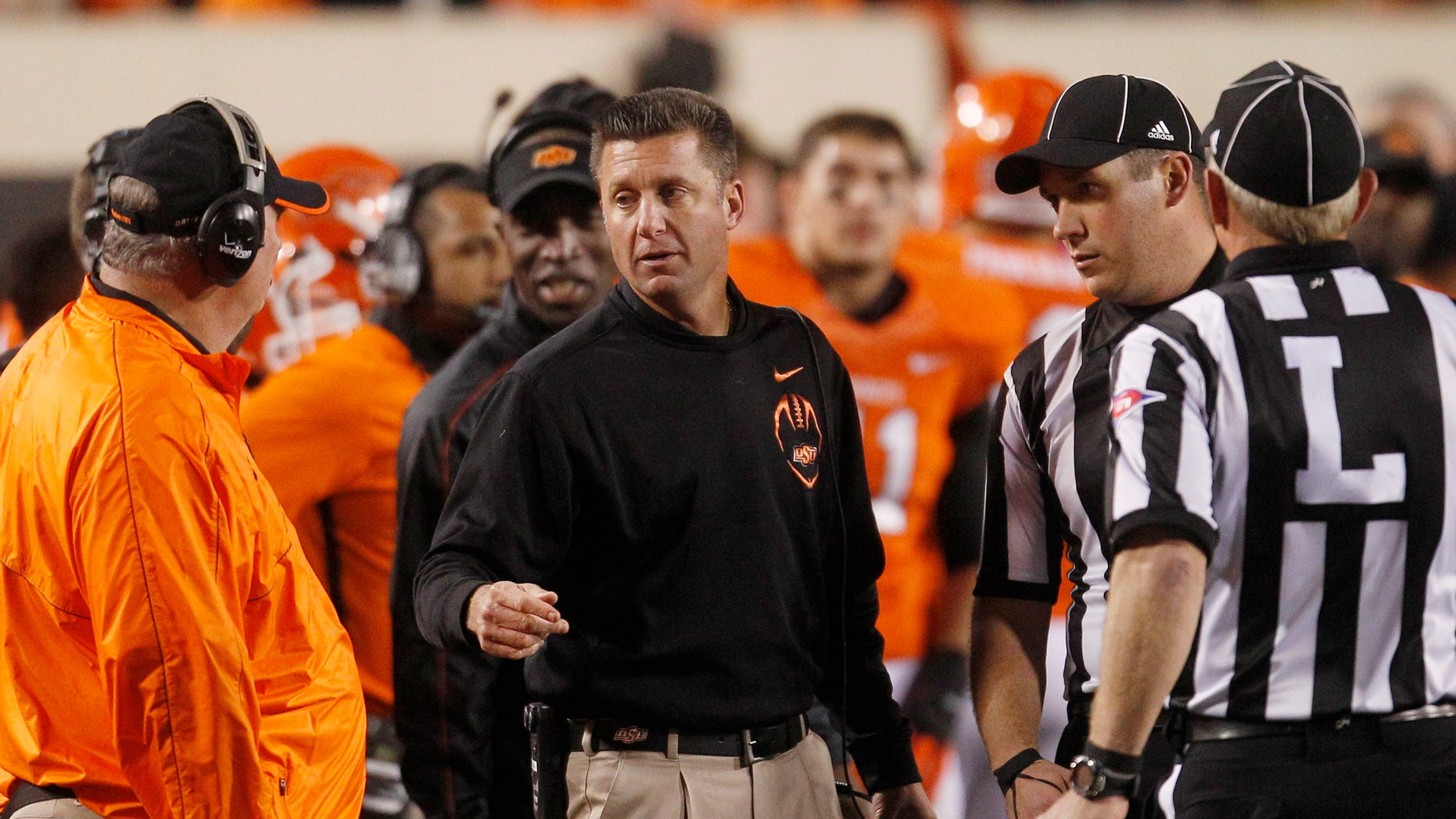 FILE - Oklahoma State head coach Mike Gundy, center, talks with defensive coordinator Bill Young, left, and officials, right, during the fourth quarter of an NCAA college football game against Texas Tech in Stillwater, Okla., in this Nov. 17, 2012 file photo.  Defensive coordinator Bill Young _ a coaching veteran of 45 years _ has said he doesn't know how much longer he plans to coach, although he talked Thursday Dec. 20, 2012 about recruiting and next season as if he will be back.(AP Photo/Sue Ogrocki, File)