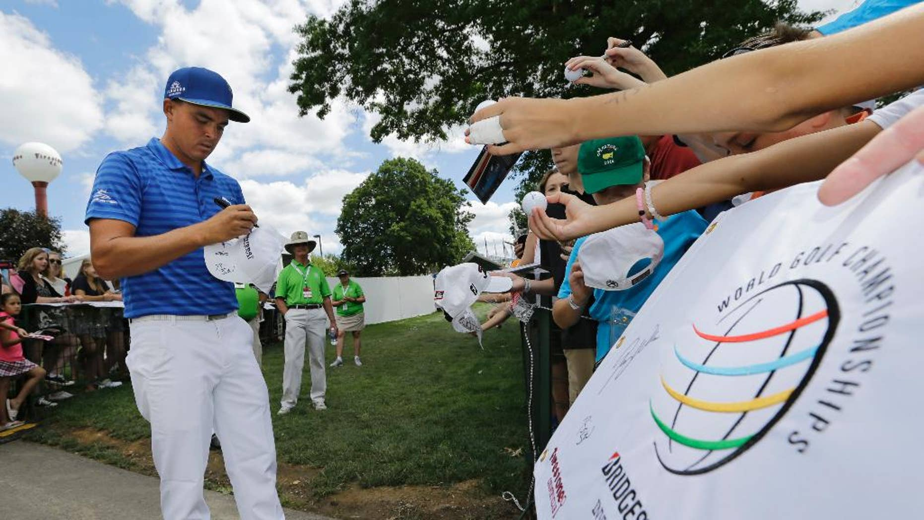 Rickie Fowler signs autographs during the practice round of the Bridgestone Invitational golf tournament at Firestone Country Club, Wednesday, June 29, 2016, in Akron, Ohio. (AP Photo/Tony Dejak)