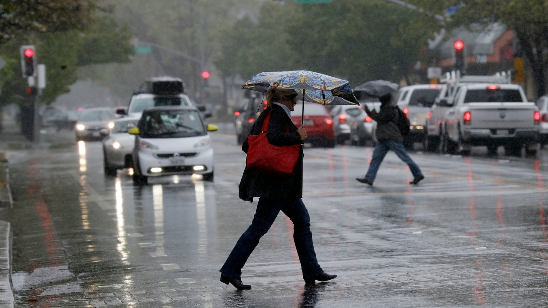 Pedestrians shield themselves from the rain with umbrellas Friday, April 6, 2018, in Santa Rosa, Calif.