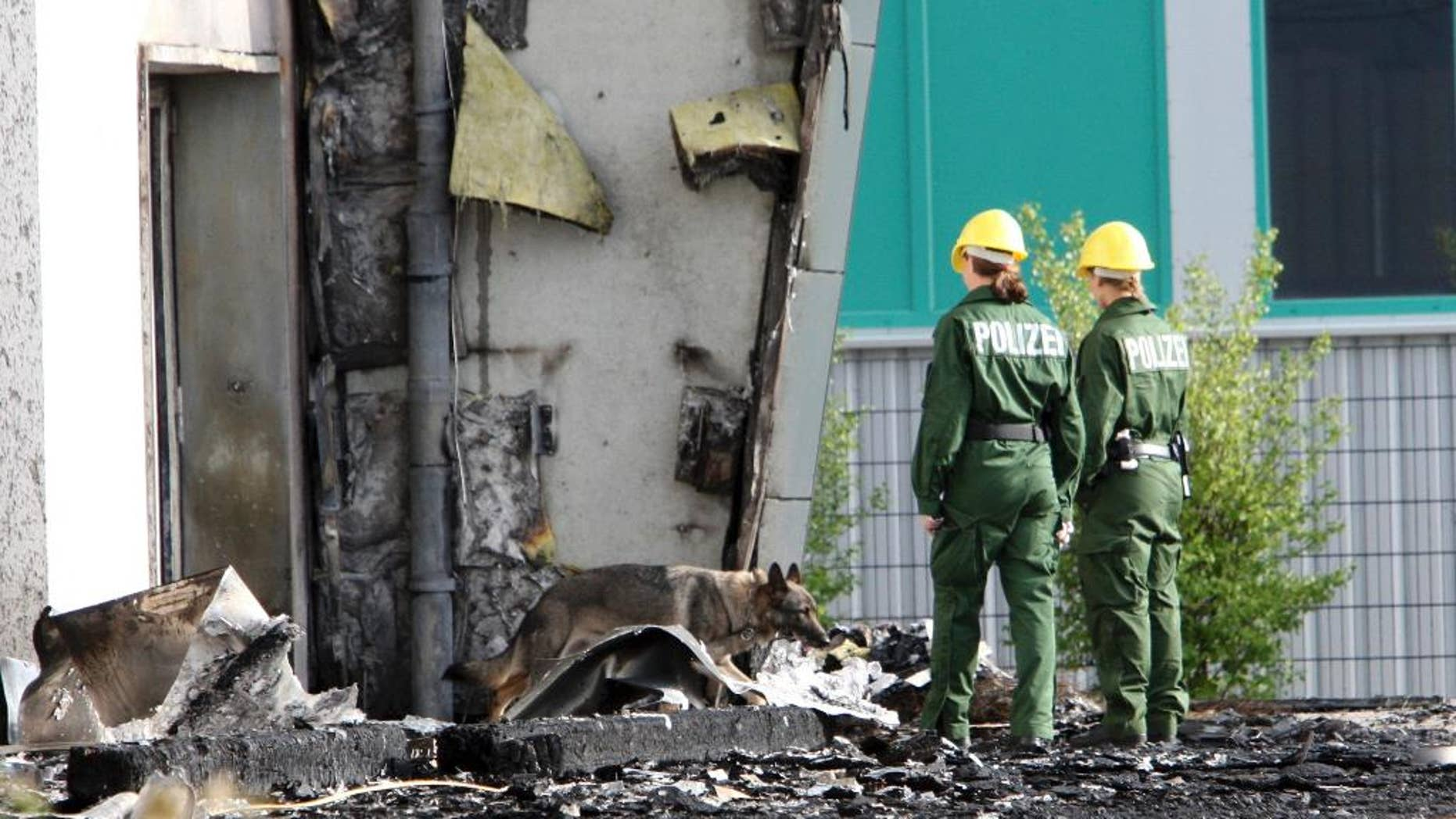 FILE - In this Aug. 26, 2015 file picture police officers and their sniffer dog examine the ruins of a burned out gym in Nauen, Germany. A German court has convicted a far-right politician for burning down the  building intended as housing for refugees. The Potsdam court sentenced 29-year-old Maik Schneider, a member of the National Democratic Party, to eight years imprisonment for arson Thursday. Feb. 9, 2017.   ( Nestor Bachmann/dpa via AP,file)