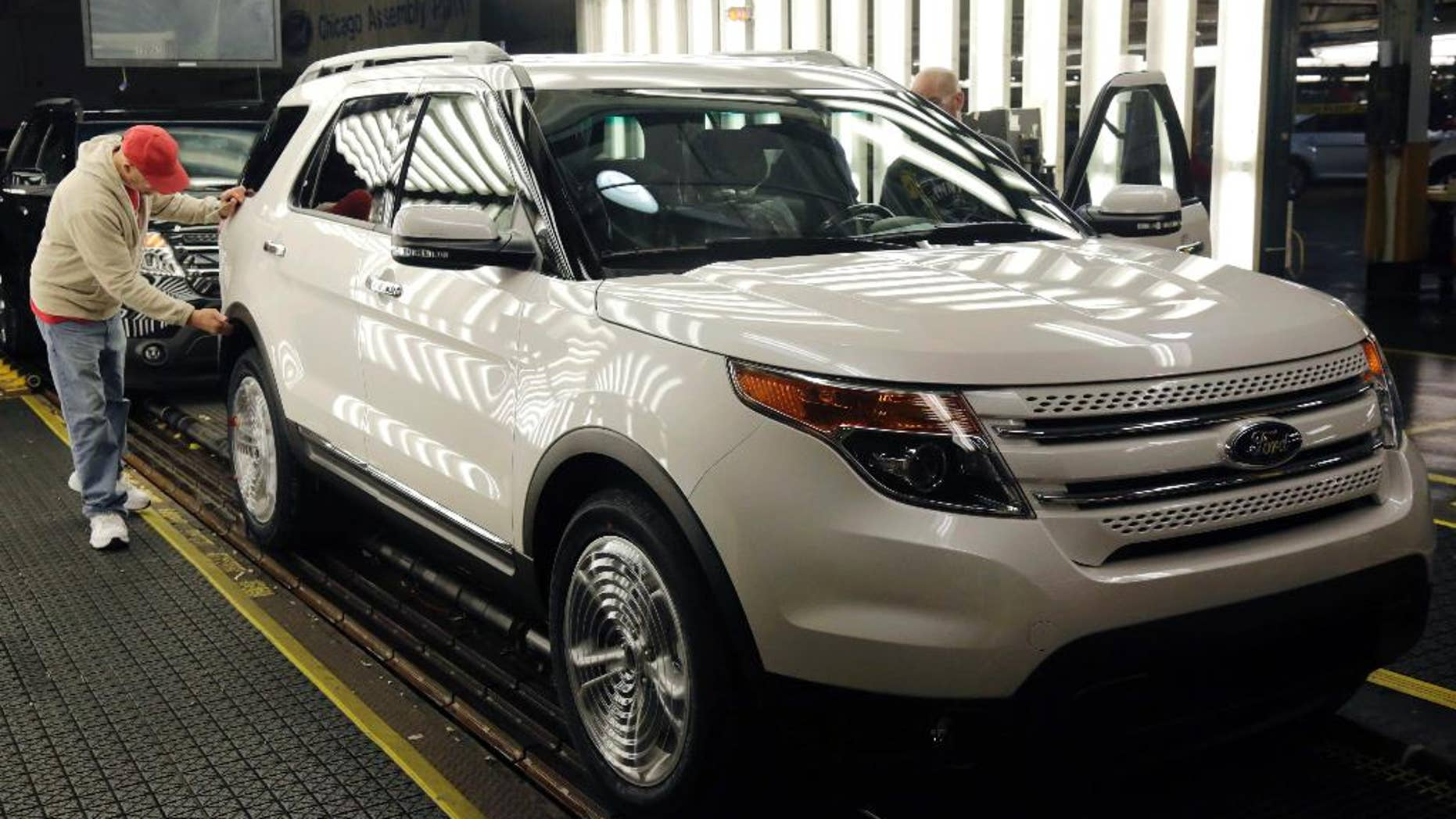 In this Oct. 22, 2014 photo, workers perform final inspections on 2015 Ford Explorers on the assembly line at the Chicago Ford Assembly Plant in Chicago. The Commerce Department releases its January report on durable goods on Thursday, Feb. 26, 2015. (AP Photo/M. Spencer Green)