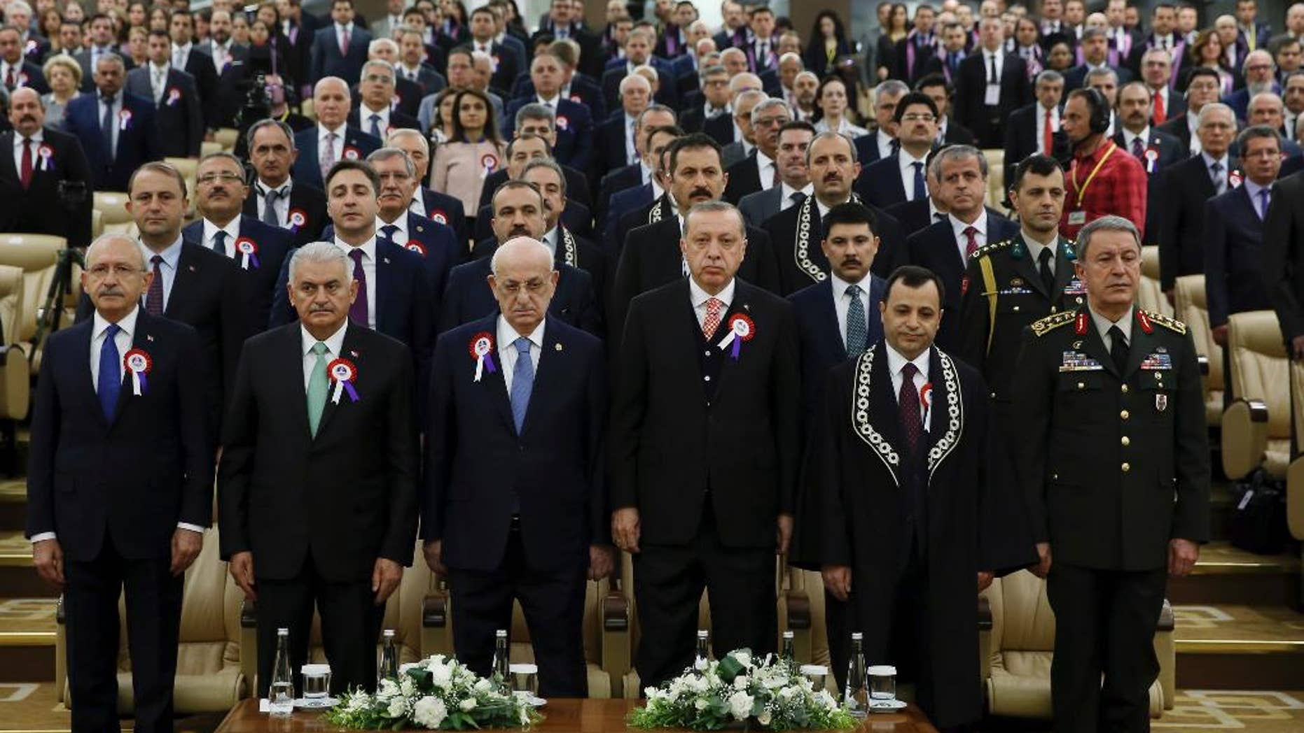 Turkey's President Recep Tayyip Erdogan, 4th left, accompanied by, from left to right, Kemal Kilicdaroglu, leader of the Republican People's Party (CHP), Prime Minister Binali Yildirim, Ismail Kahraman, Speaker of the Grand National Assembly of Turkey, Turkish Constitutional Court Chairman Zuhtu Arslan and Chief of the General Staff of the Turkish Armed Forces, Hulusi Akar, attend a ceremony as part of the 55th anniversary of the founding of Turkey's Constitutional Court, in Ankara, Turkey, on Tuesday, April 25, 2017. Legislators representing Europe's top human rights body, the Strasbourg-France-based Parliamentary Assembly of the Council of Europe, on Tuesday voted in favour of re-opening monitoring procedures in Turkey in a move that reflects its strong concern over the functioning of democratic institutions in the country.(Press Presidency Press Service Pool Photo via AP)