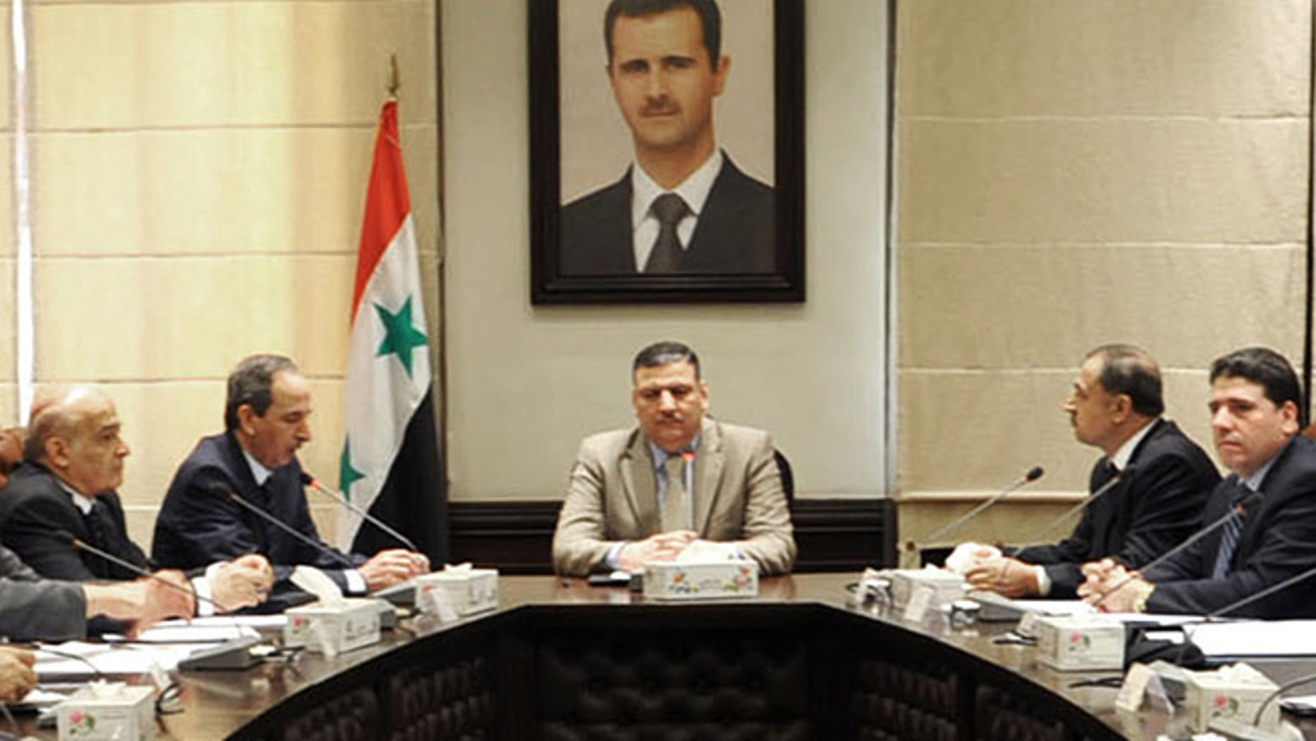 In this undated photo released by the Syrian official news agency SANA on Sunday, Aug. 5, 2012, Syrian Prime Minister Riad Hijab, center, speaks under the portrait of the Syrian President Bashar Assad during a meeting in Damascus, Syria. Hijab defected and fled to neighboring Jordan, a Jordanian official and a rebel spokesman said Monday, Aug. 6, 2012.