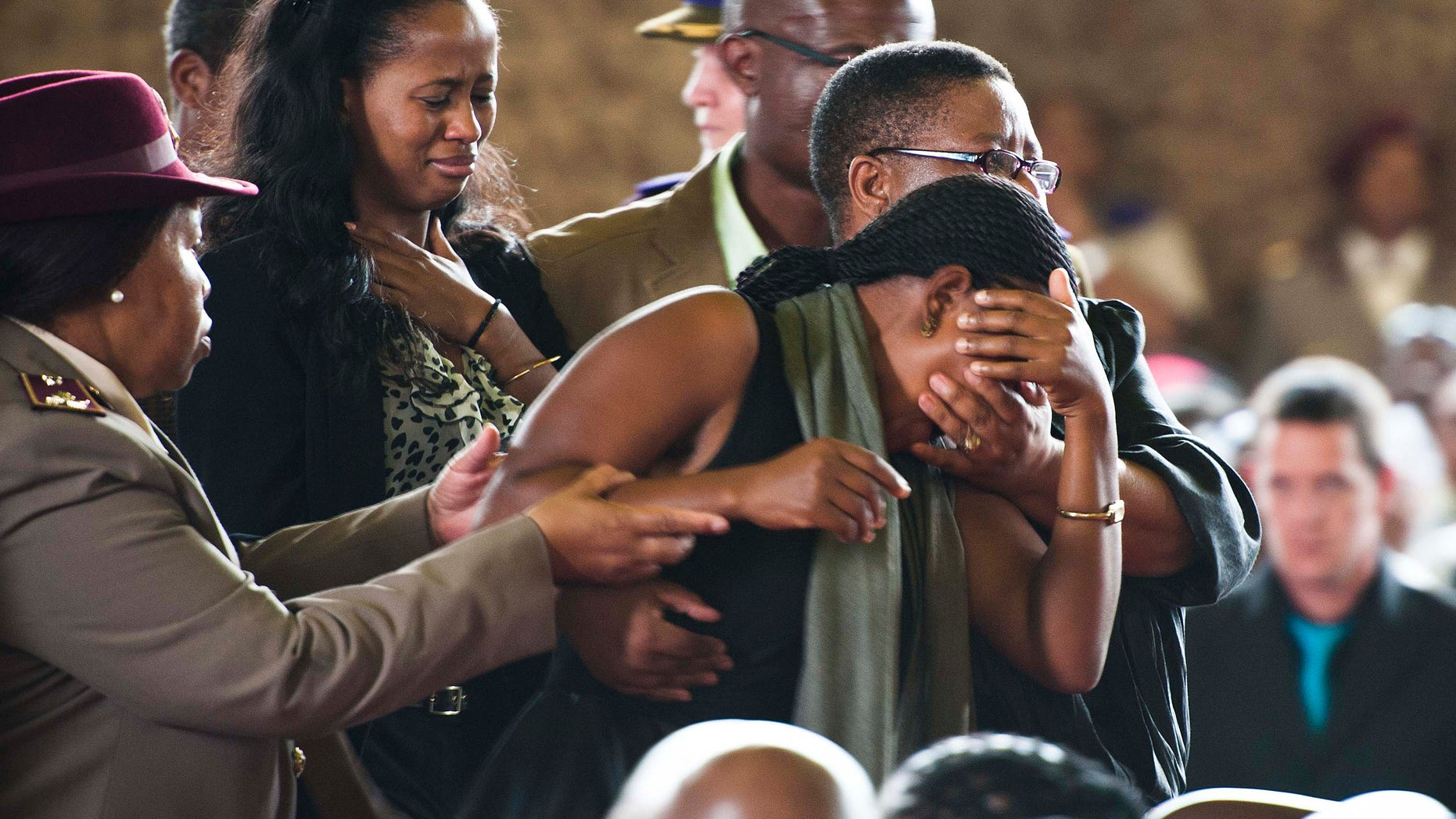 A mourner breaks down during a memorial service for 13 South African soldiers killed in Central African Republic last week, at an air force base in Pretoria, South Africa, Tuesday, April 2, 2013. The service took place amid strident debate about why the troops were deployed  and accusations that they were sent to protect business interests of a company allied to the ruling African National Congress , charges which president Jacob Zuma denied. (AP Photo)