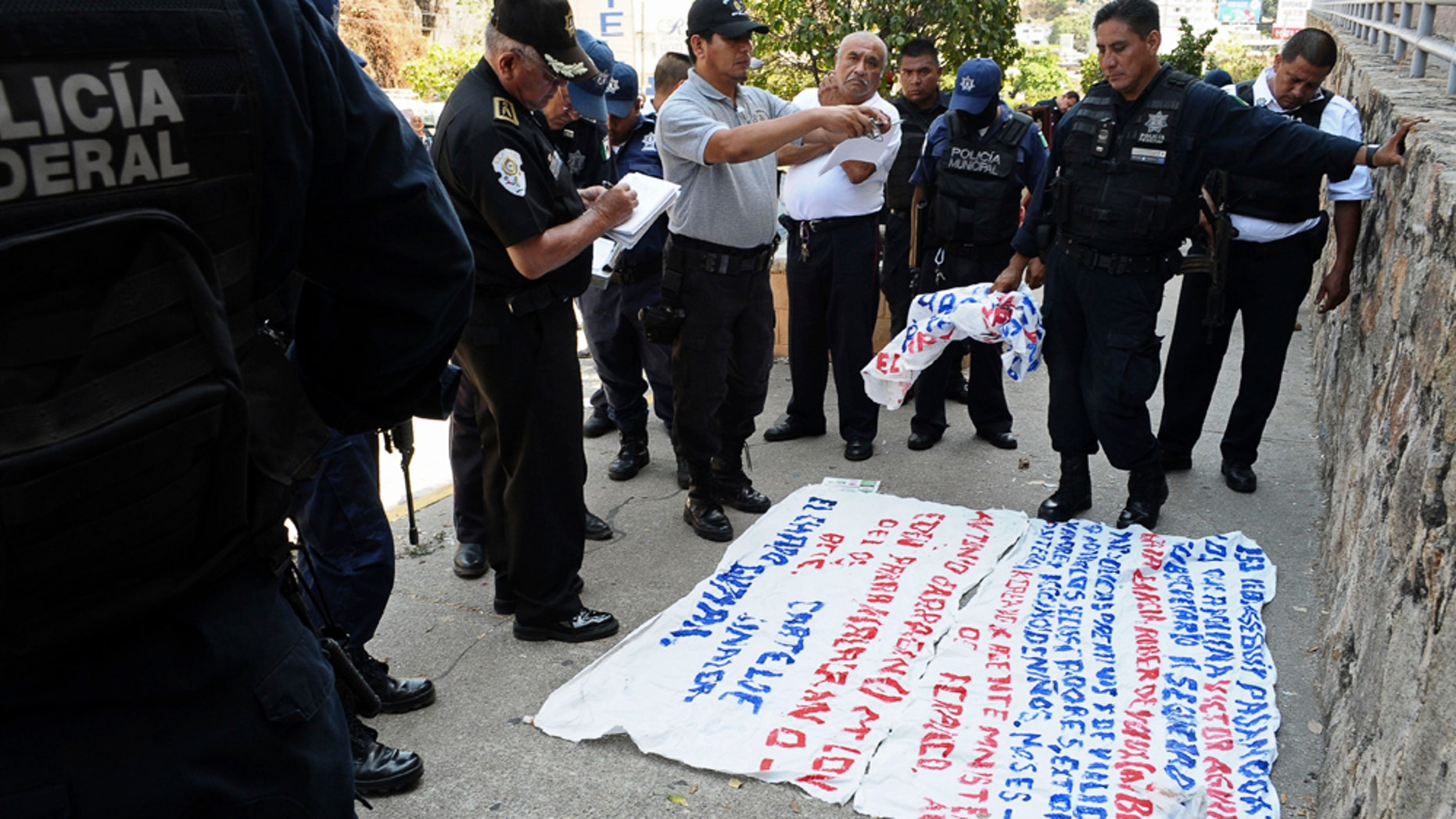 Police stand around a warning message painted on a banner left near the site where five dismembered bodies were found on the sidewalk next to a car in the Pacific resort city of Acapulco, Mexico Friday March 25, 2011. The bodies,  four of them police officers who were abducted hours earlier, according to police reports, were found just a few blocks from where Mexico's President Felipe Calderon and Guerrero State Governor Zeferino Torreblanca inaugurated the city's annual Tourism Fair for international tour operators and industry officials. Calderon has declared 2011 the Year of Tourism as Acapulco is facing record levels of violence from warring cartels. (AP Photo/Bernandino Hernandez)