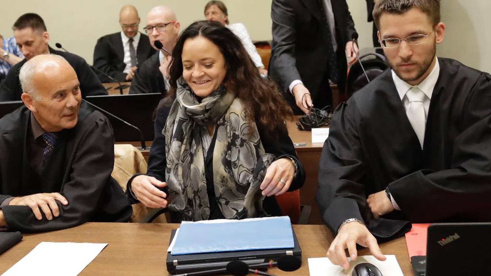 Terror suspect Beate Zschaepe arrives at the court room besides her lawyers Hermann Borchert, left, and Mathias Grasel in Munich, Germany, Thursday, Sept. 29, 2016. Zschaepe is accused of being involved in 10 neo-Nazi murders of the National Socialist Underground group, which allegedly killed eight Turkish men, a Greek and a policewoman between 2000 and 2007. (AP Photo/Matthias Schrader)
