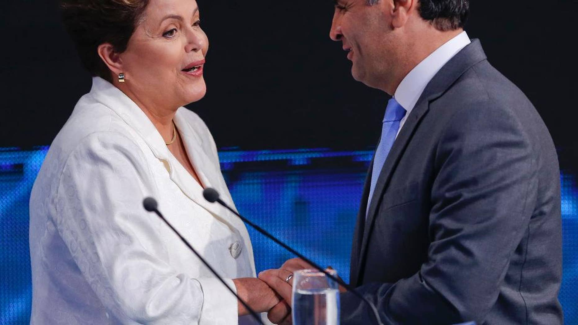 Brazil's President Dilma Rousseff, presidential candidate for re-election of the Workers Party, PT , left, shakes hands with Aecio Neves, presidential candidate of the Brazilian Social Democracy Party, PSDB, at the end of a presidential debate in Sao Paulo, Brazil, Tuesday, Oct. 14, 2014. Rousseff and Neves will face each other in a presidential runoff on Oct. 26. (AP Photo/Andre Penner)