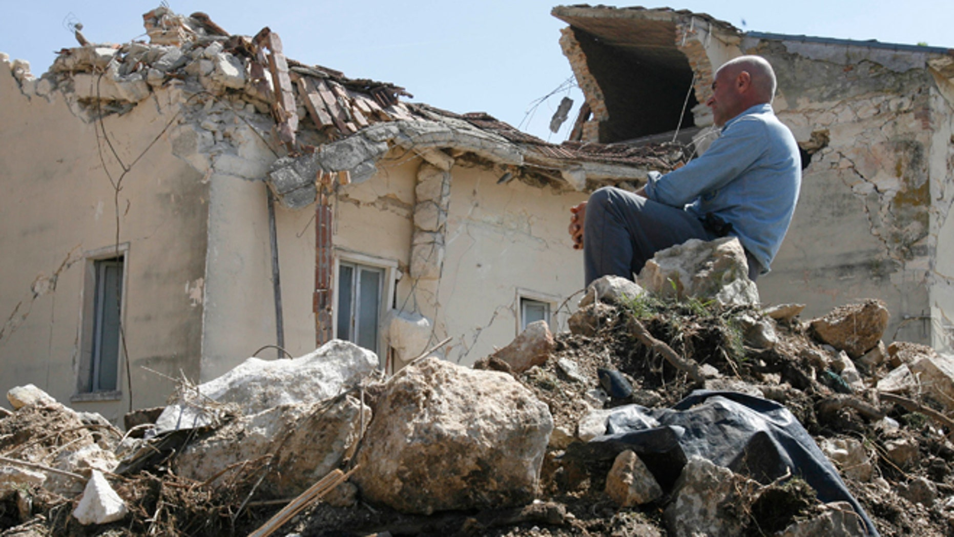 April 7, 2009: A man sits on rubbles in the village of Onna, a day after a powerful earthquake struck the Abruzzo region in central Italy.